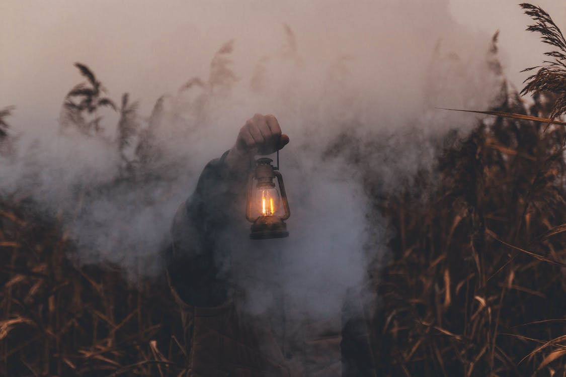 Person Holding Kerosene Lantern