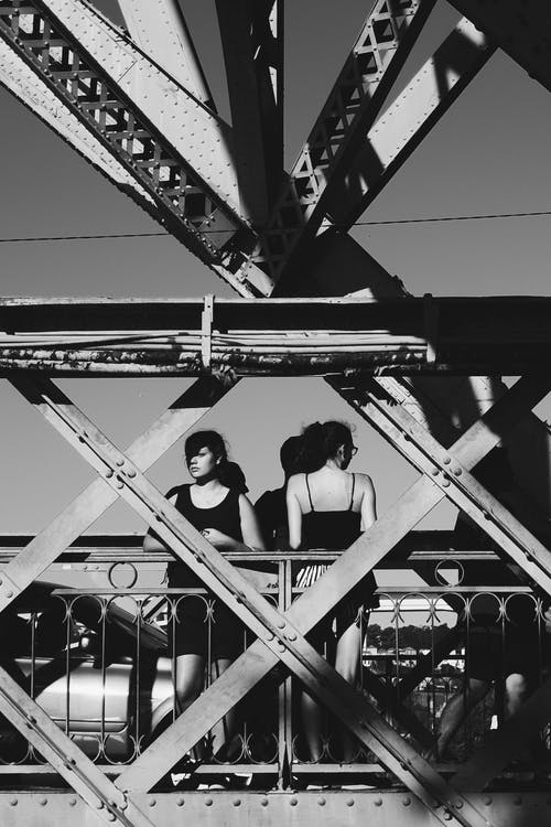 Two Woman Standing on Suspension in Grayscale Photography
