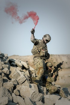 2 Soldier With Guns on Grey Pile of Rocks Holding Smoke Stick during Daytime