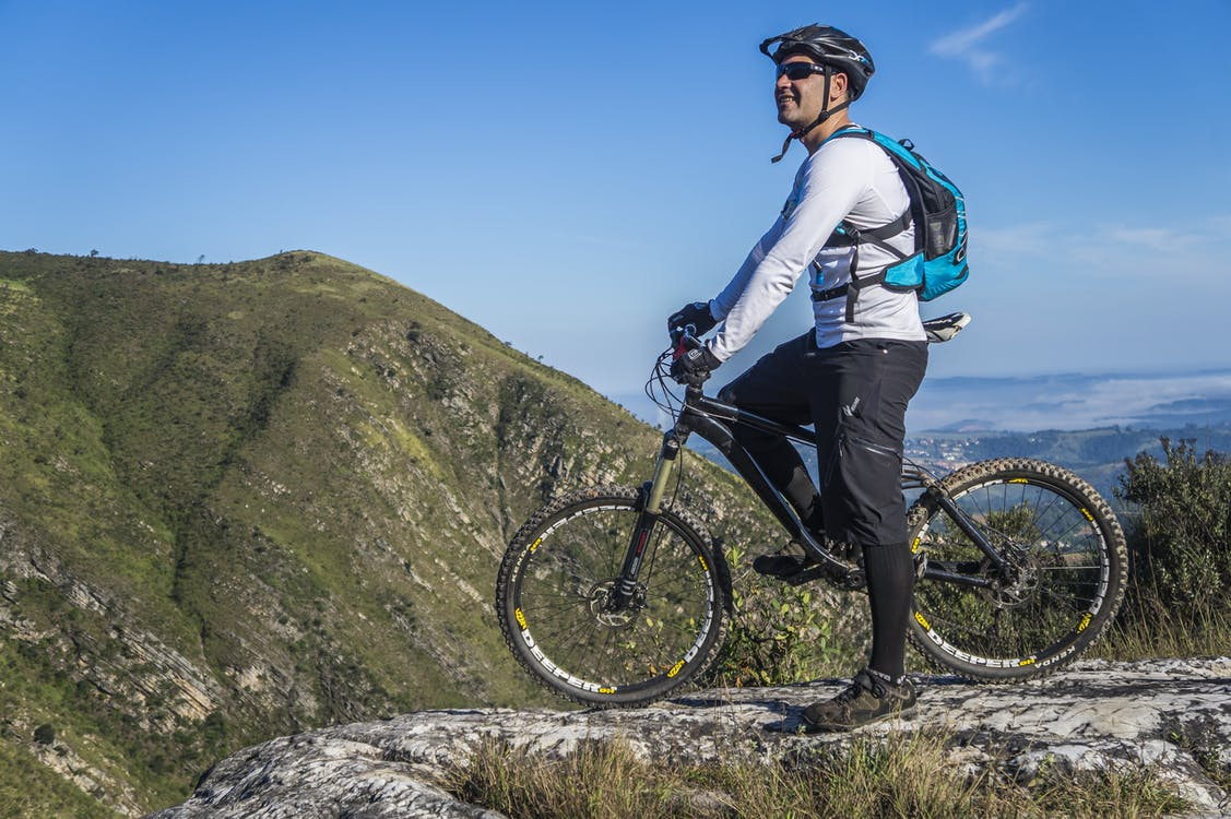 Man With White Shirt Riding Abicycle on a Mountain