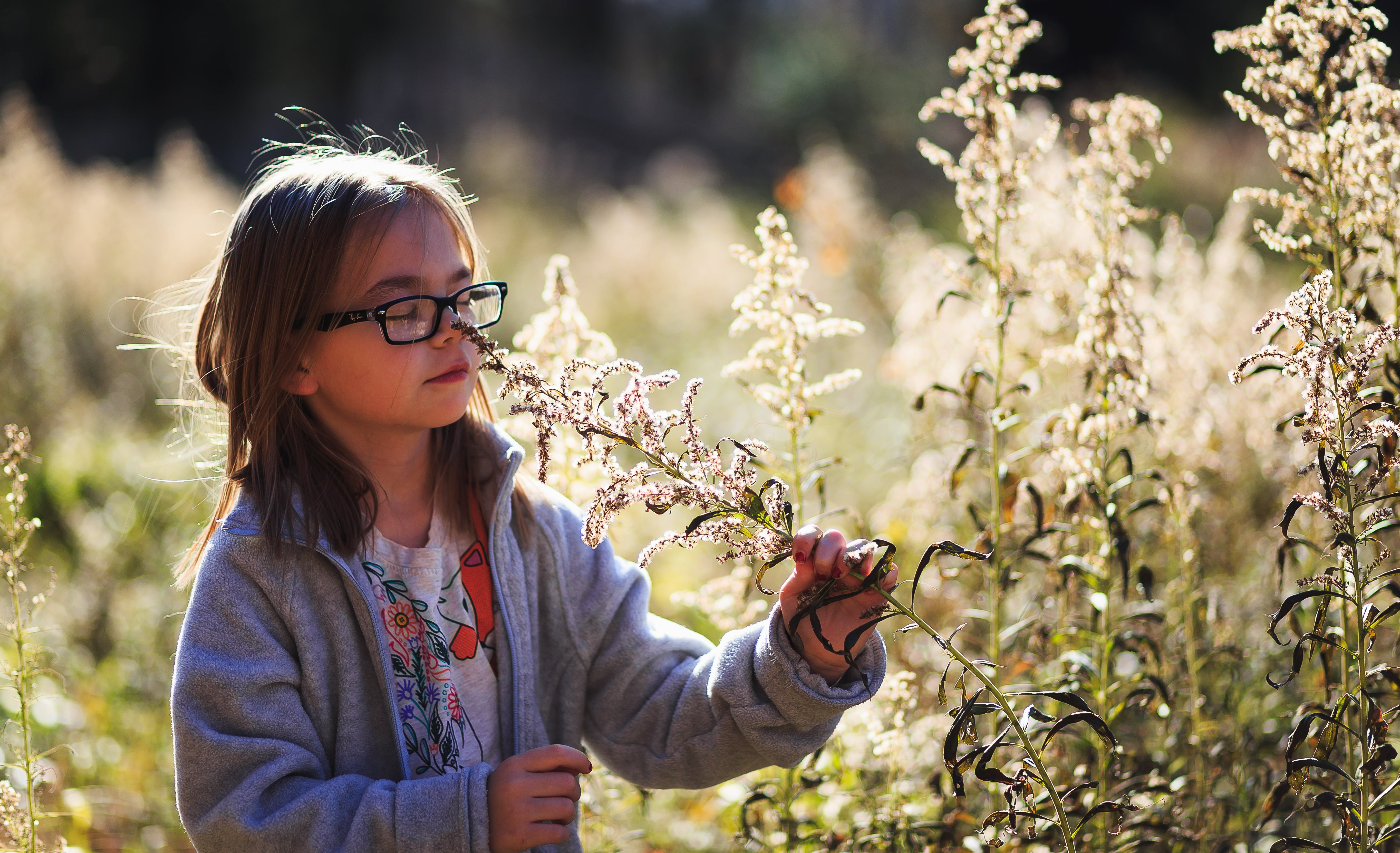 Girl Wearing Eyeglasses Smelling Flowers