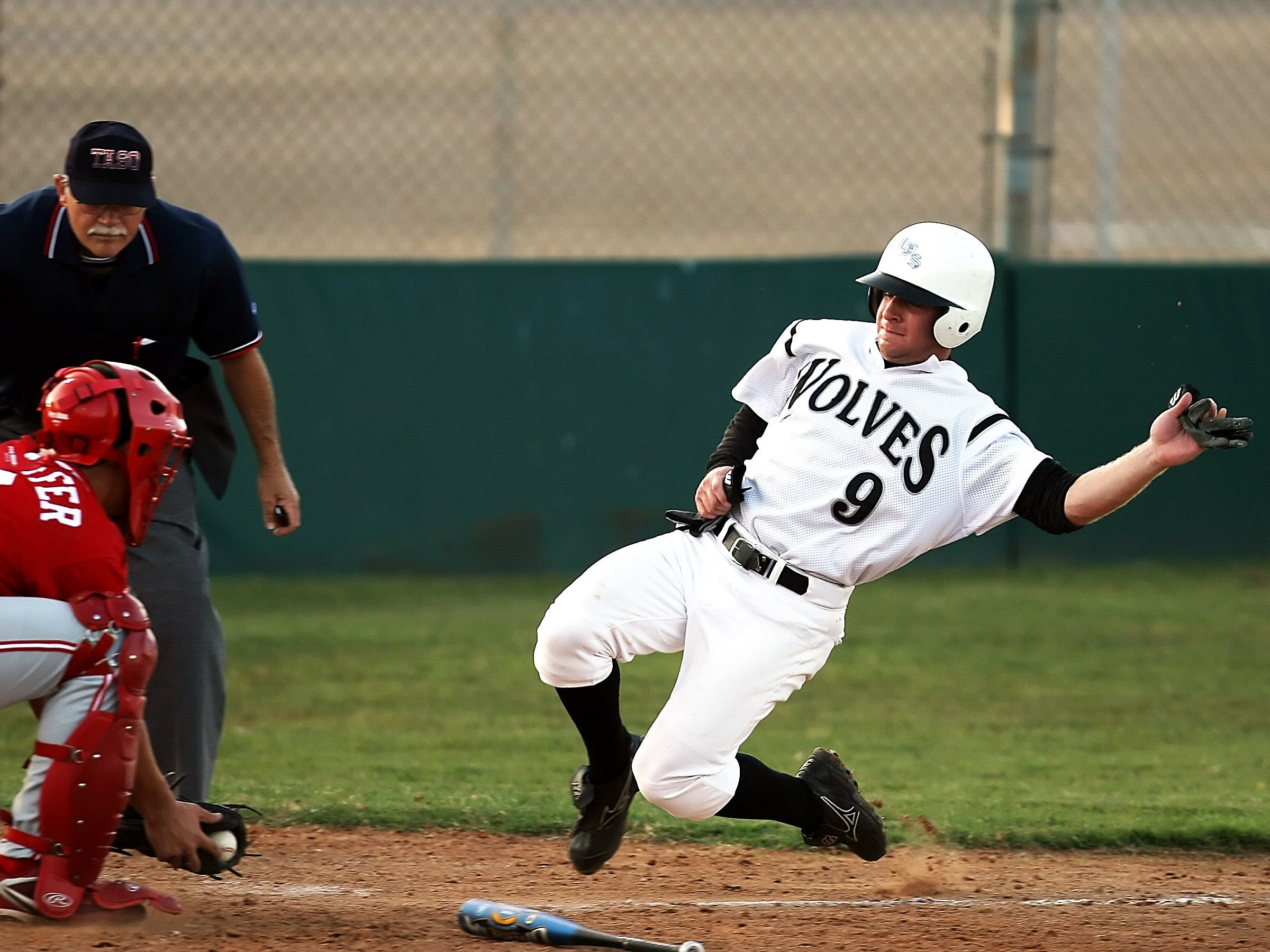 Male Baseball Player in Wolves 9 Jersey Sliding in Front of Male in Catchers Uniform Holding Baseball on Brown Mitt