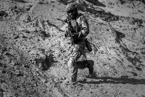Man in Army Full Combat Uniform Carrying Rifle