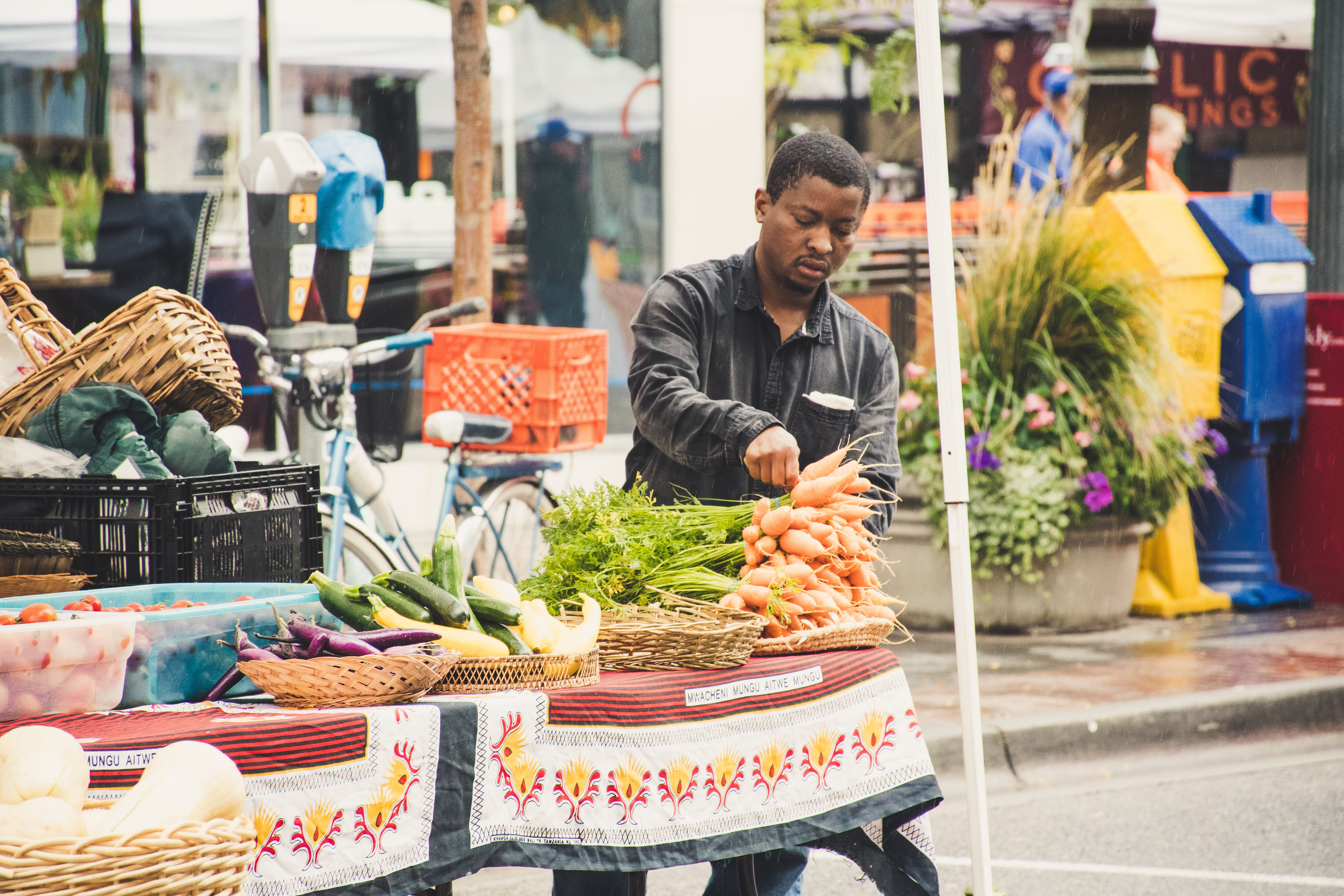 Man Standing Beside Table With Vegetables Near Buildings