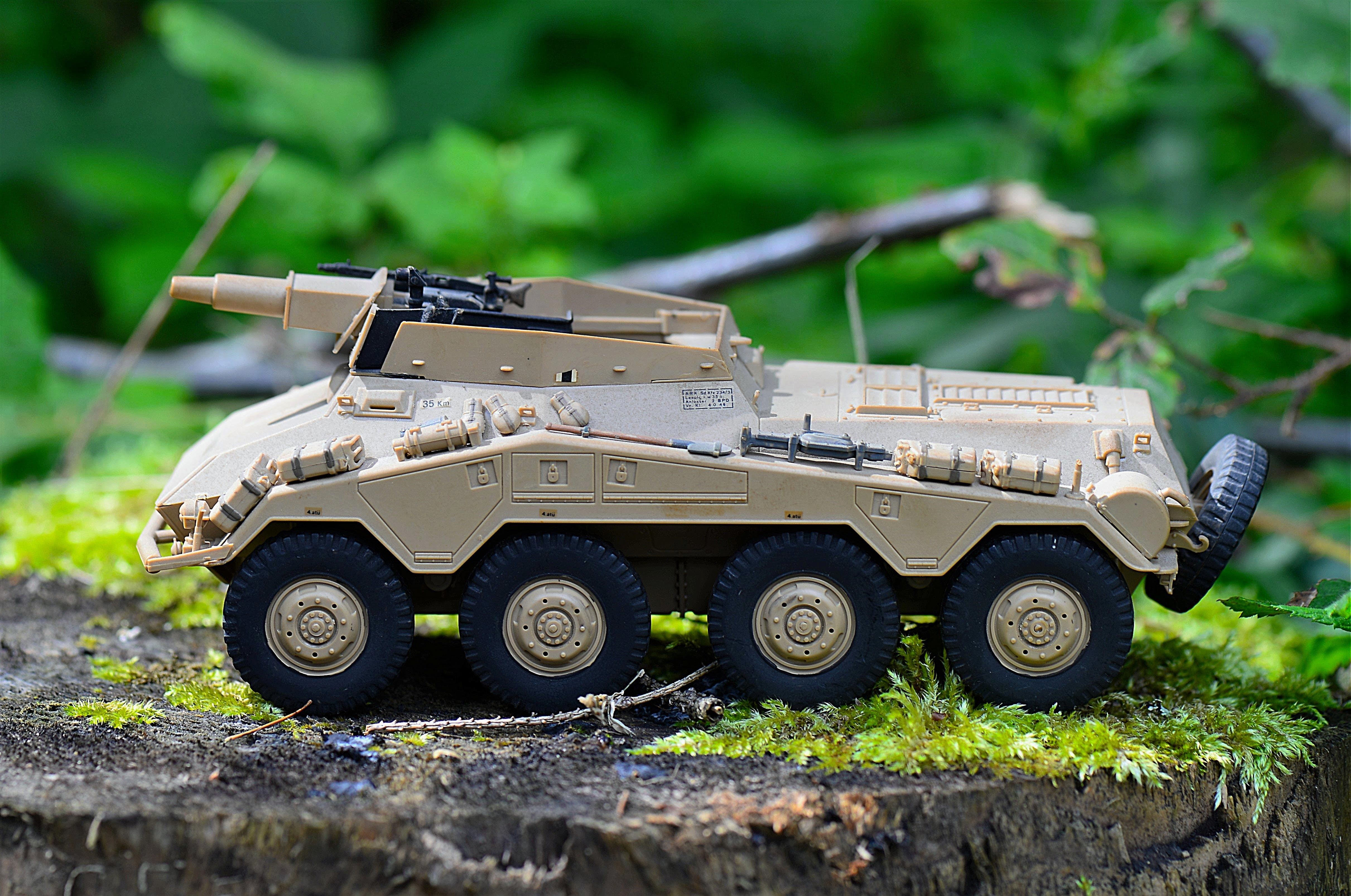 Tan Military Artillery Vehicle Toy on Wood Stump