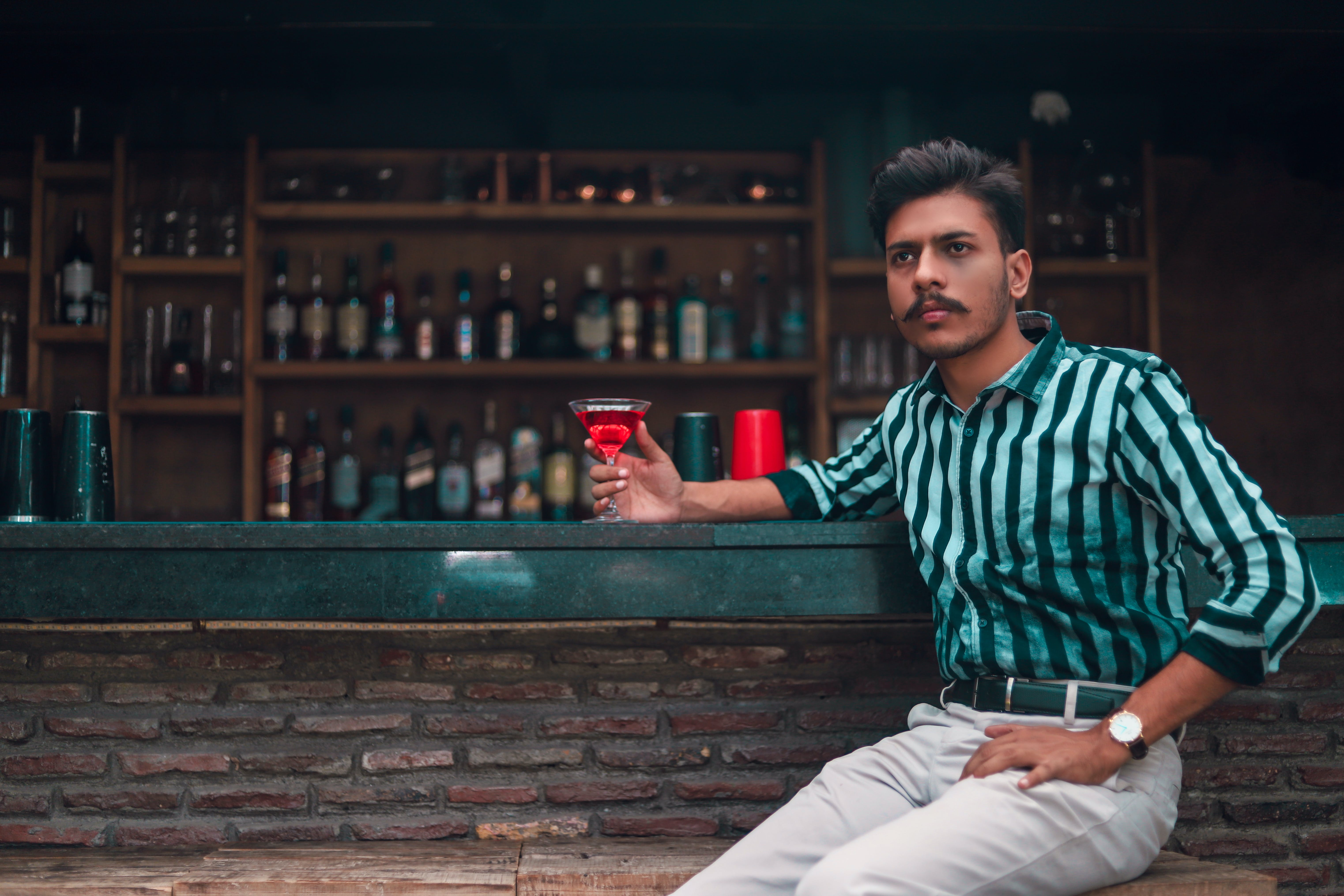 Man Sitting Holding Cocktail Glass