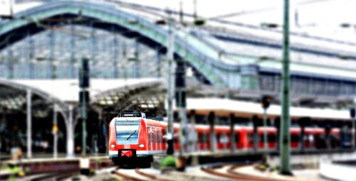 Red Train at a Green Train Station on an Overcast Day