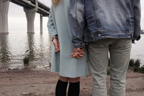 Man And Woman Holding Hands Near Body Of Water