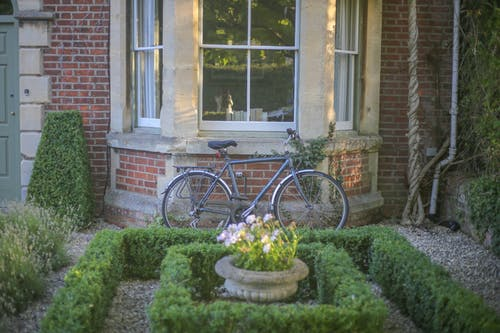 Grey Mountain Bike Leaning on Brown Wall Brick in Garden