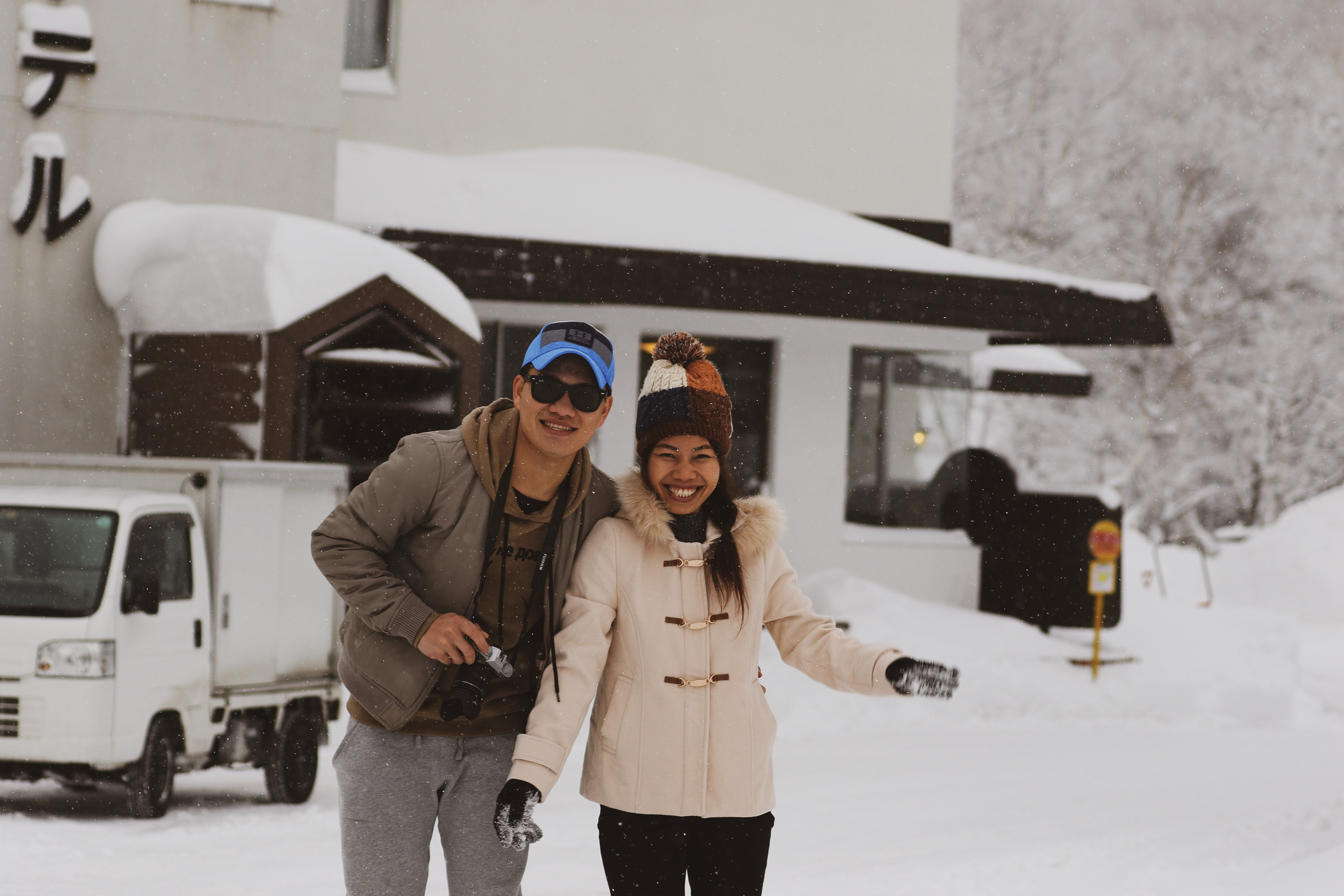 Smiling Man and Woman Standing on Snow Near White Truck Beside White and Brown House