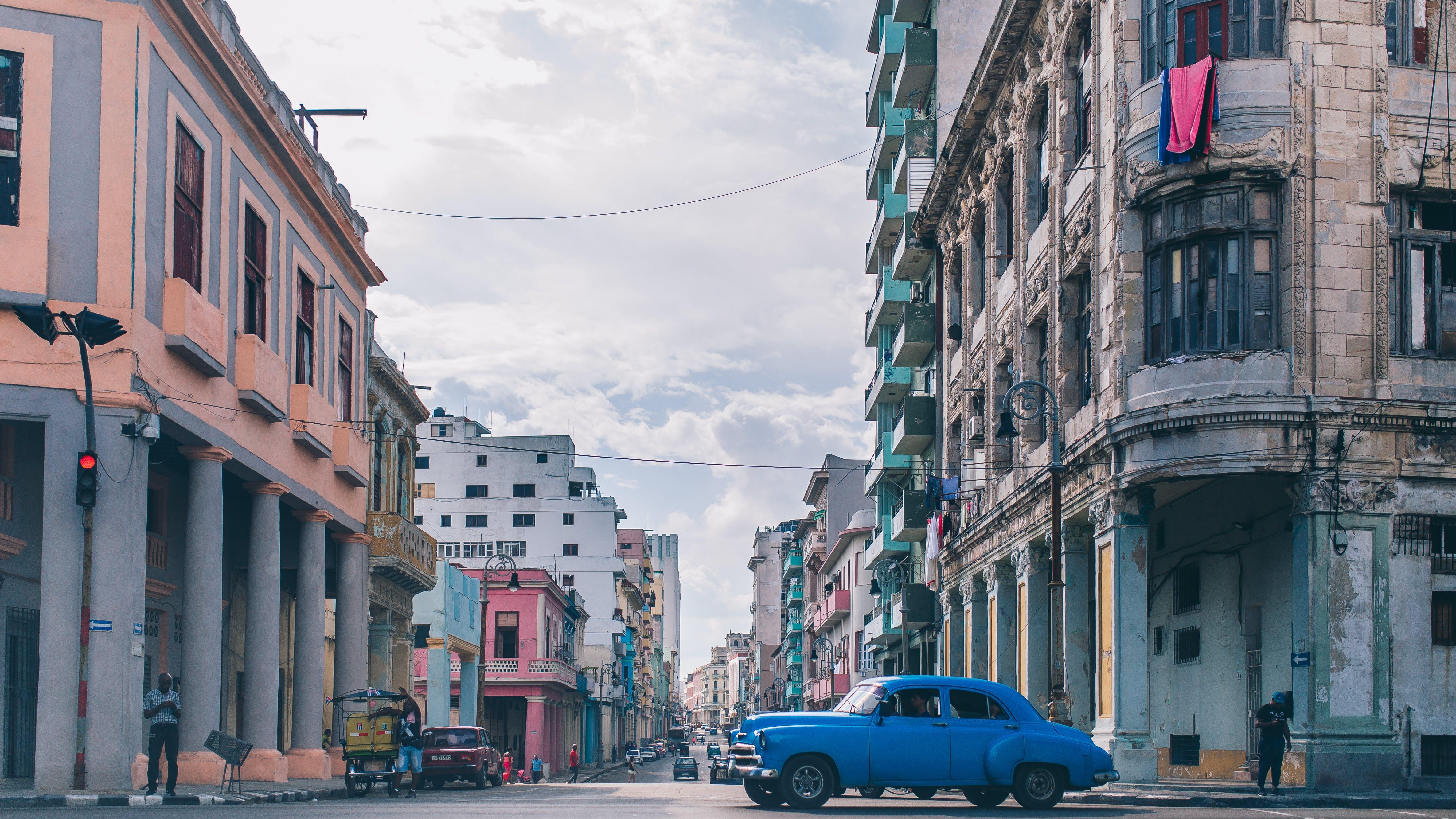 Blue Sedan on Road Between Buildings