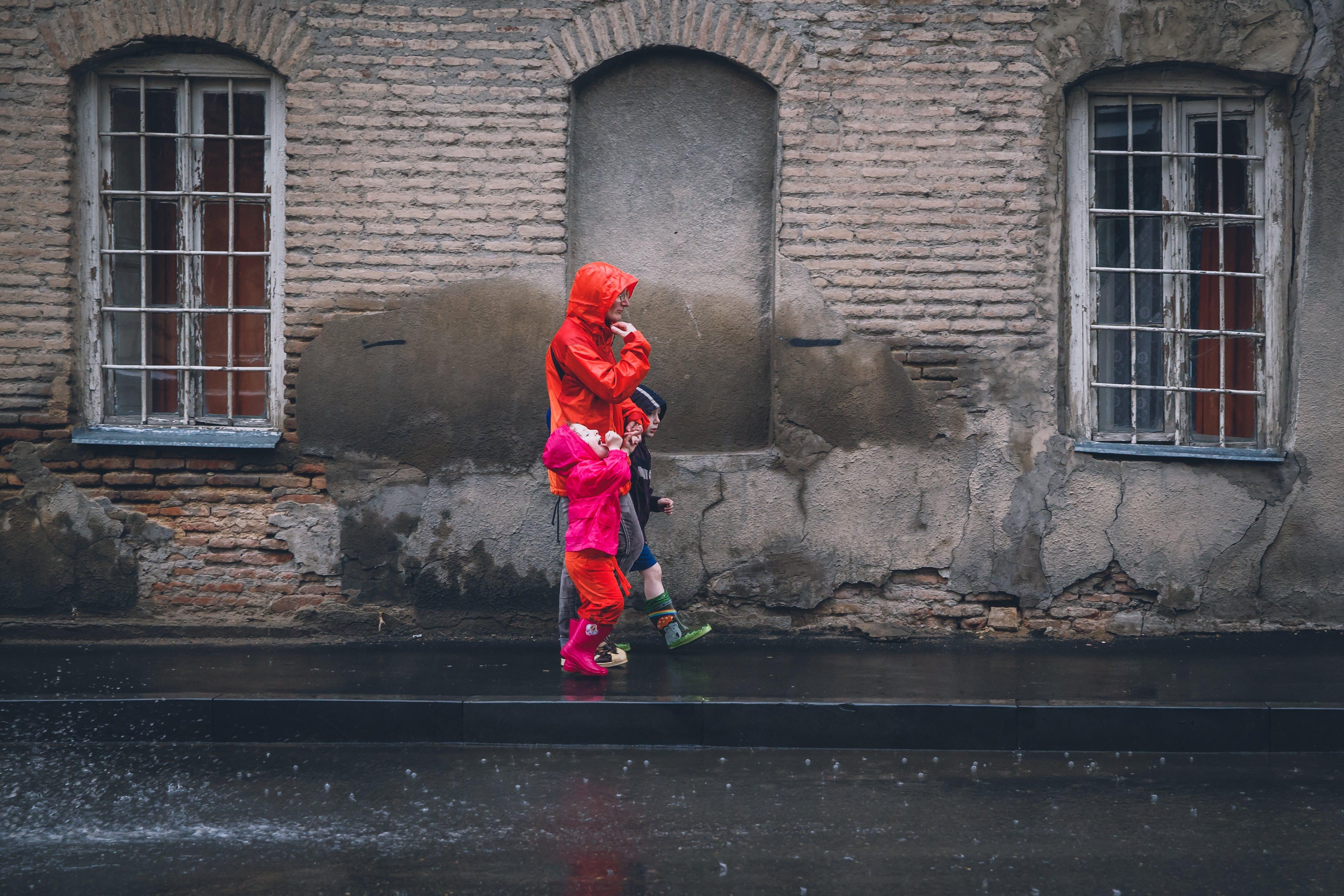 Children and Man Walking on a Sidewalk during Daytime