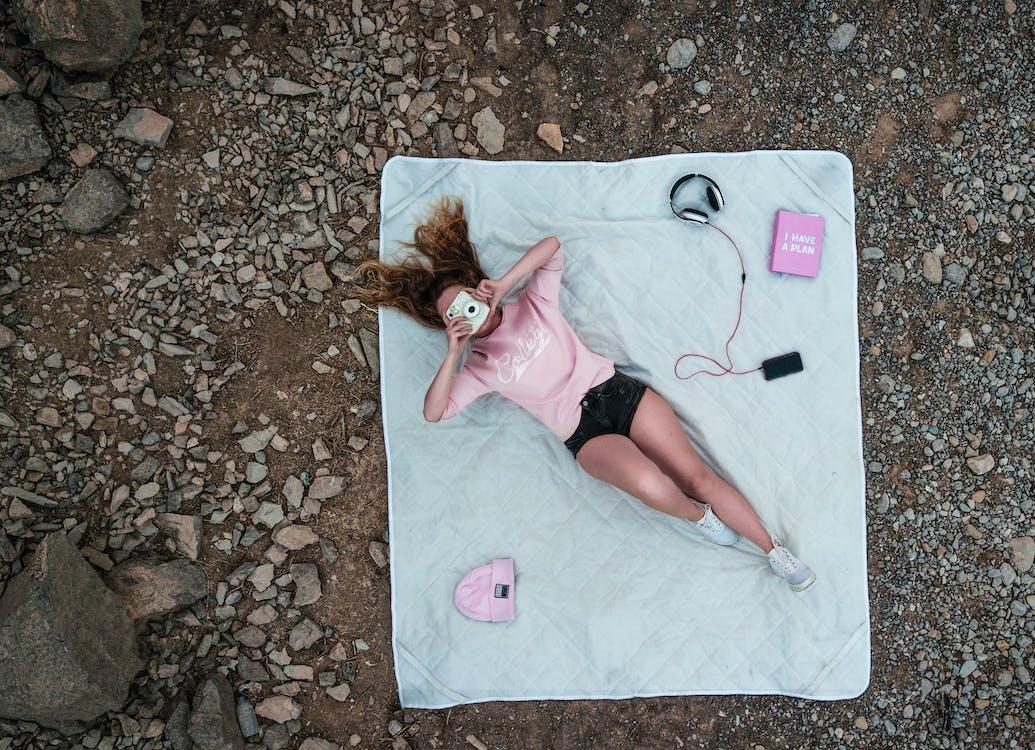 Top View Photo of Woman Lying on Mattress