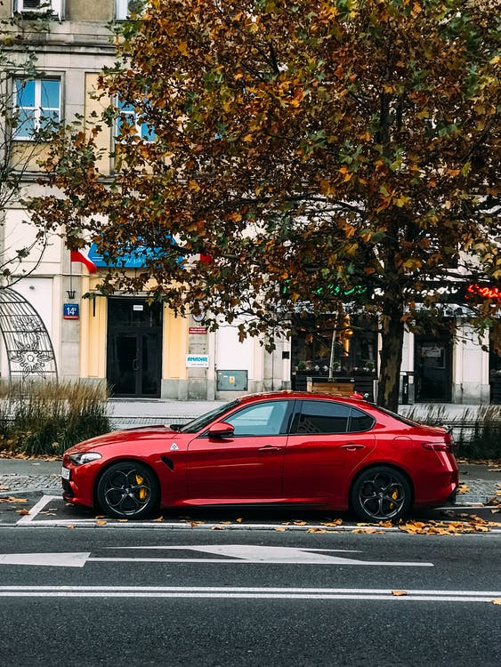 Red Sedan Parked on the Side of the Road