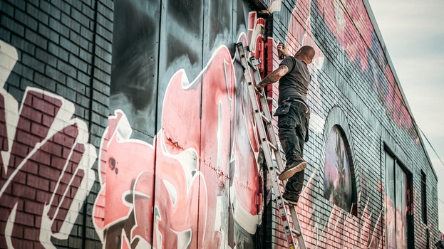 Man in Gray Shirt Standing on Gray Steel Ladder Painting Black White and Red Graffiti on Concrete Wall Outdoors