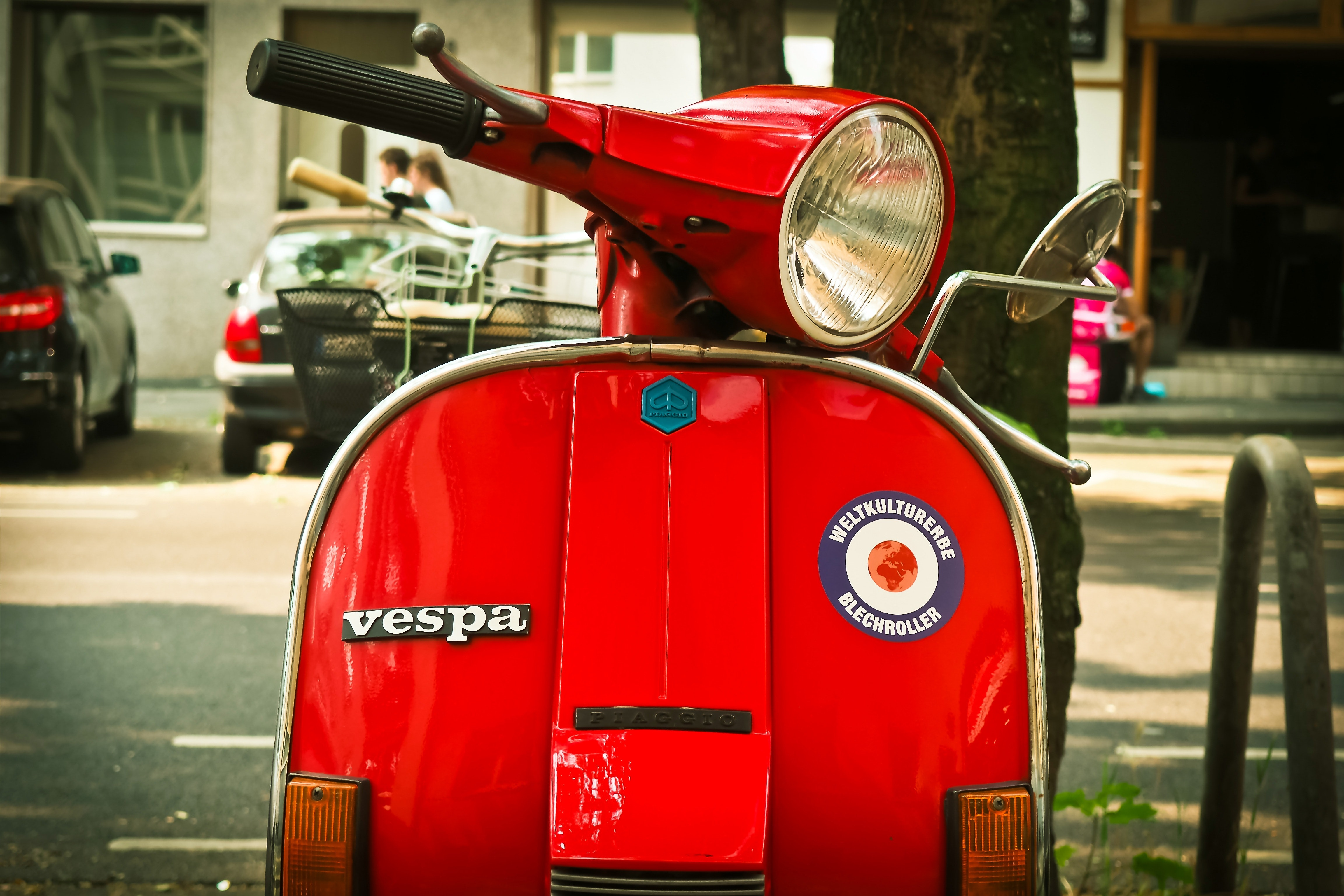 red vespa motor scooter parked near tree during daytime free stock
