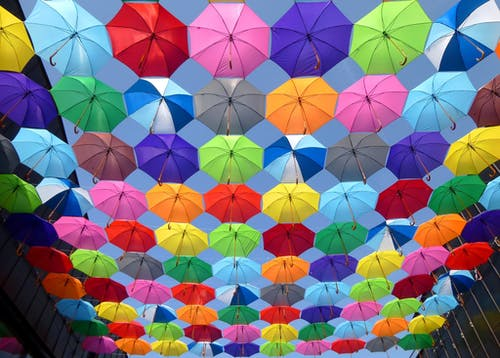 Yellow Blue Red Pink Purple Green Multicolored Open Umbrellas Hanging on Strings Under Blue Sky
