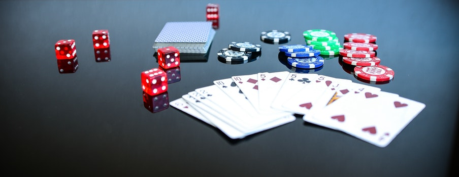 Playing Cards Beside Poker Chips and Dice