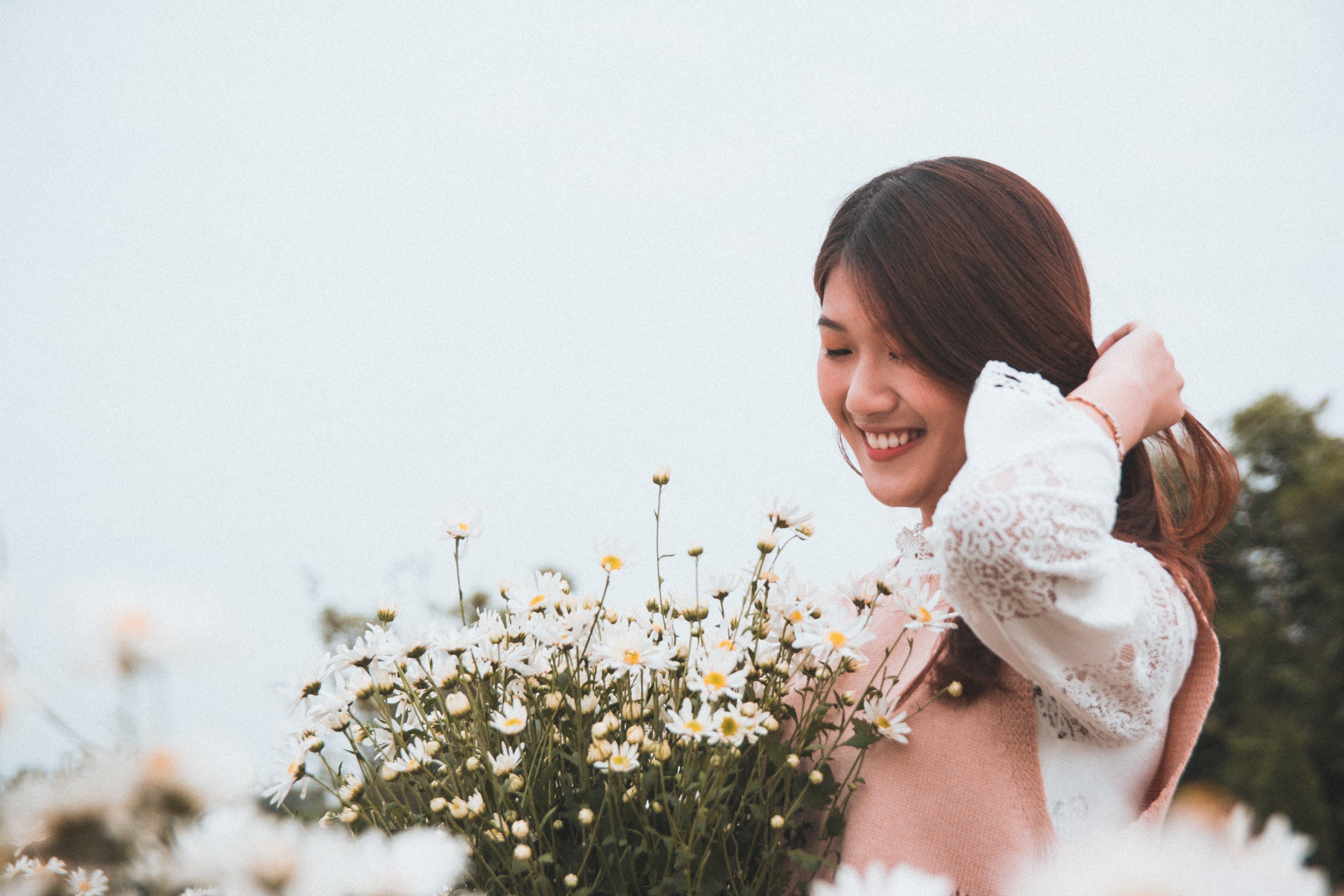 Woman Smiling Near Flowers