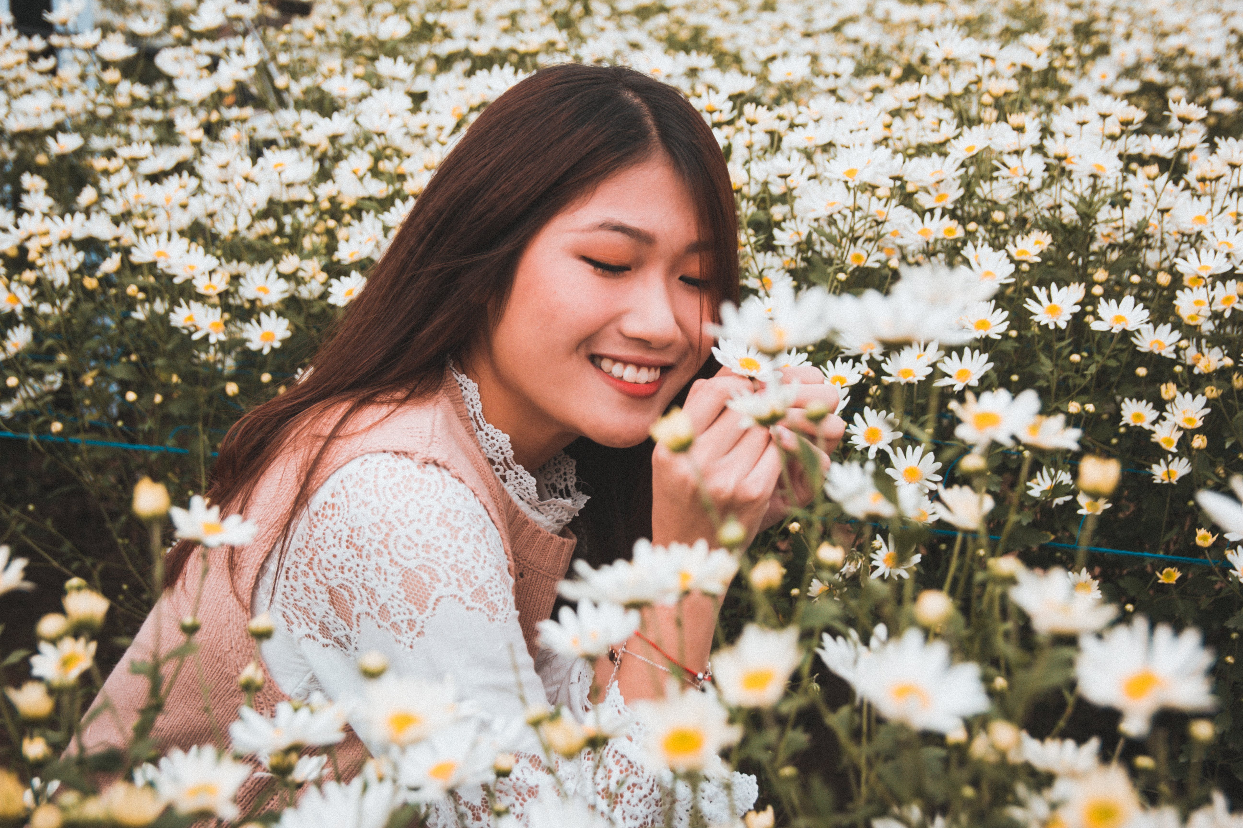 Photo of Woman Smiling Surrounded by Daisy Flower Field