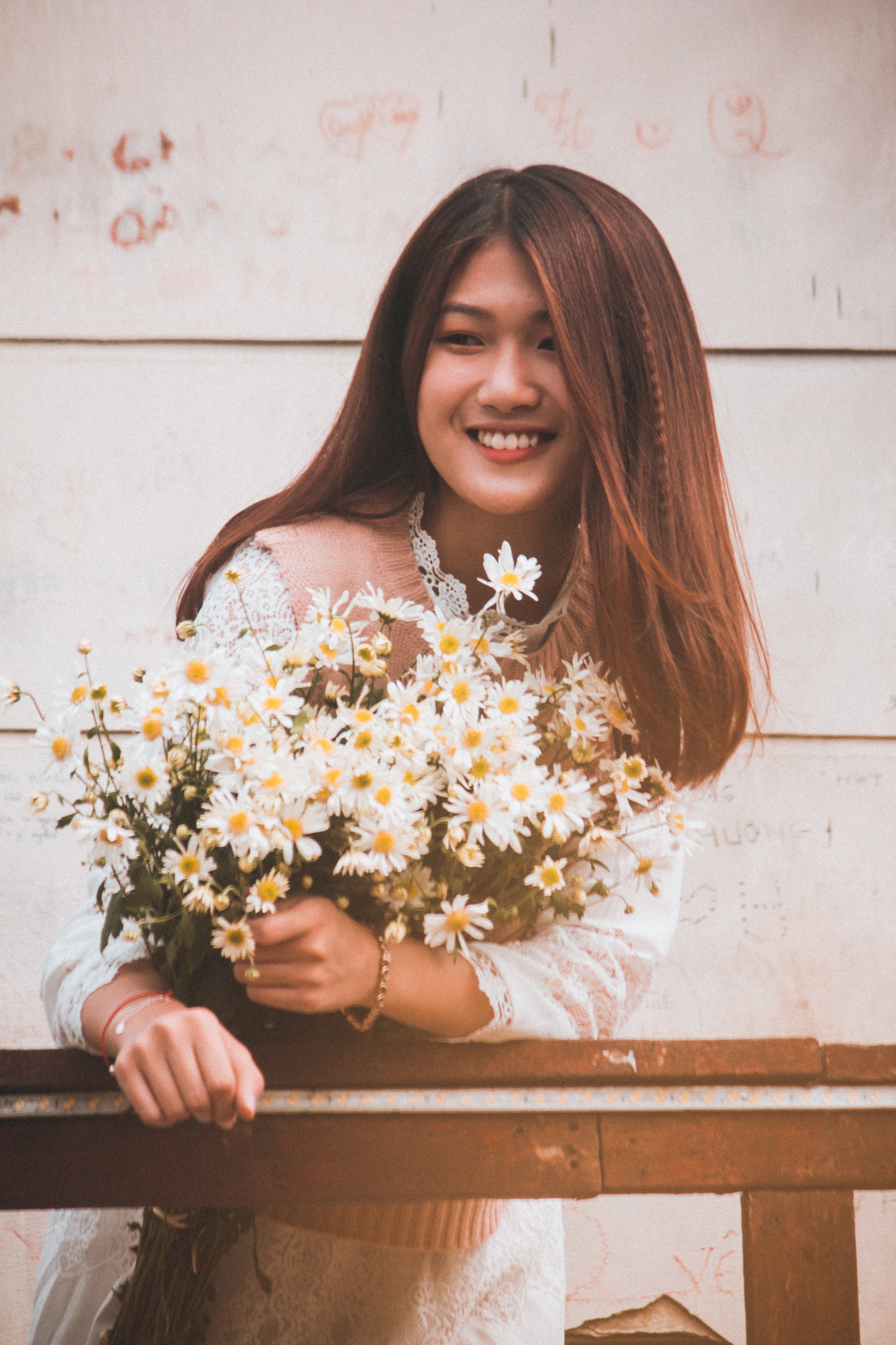 Photo of Smiling Woman Wearing White Long-sleeved Dress Holding White Daisy Bouquet