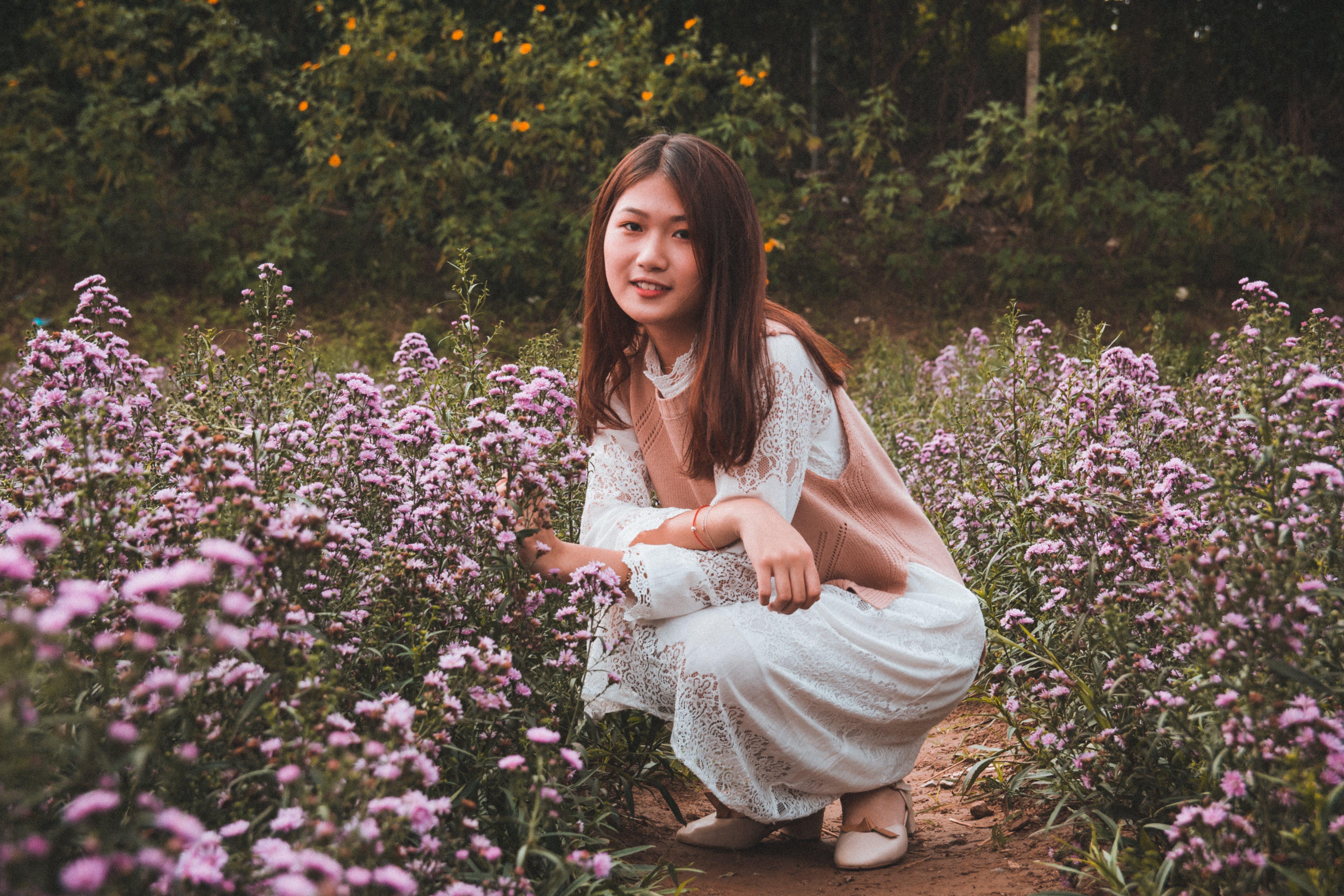 Woman Squatting Beside Purple Flowers