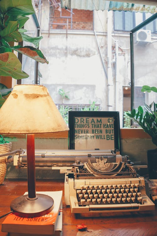 White Typewriter Beside Table Lamp