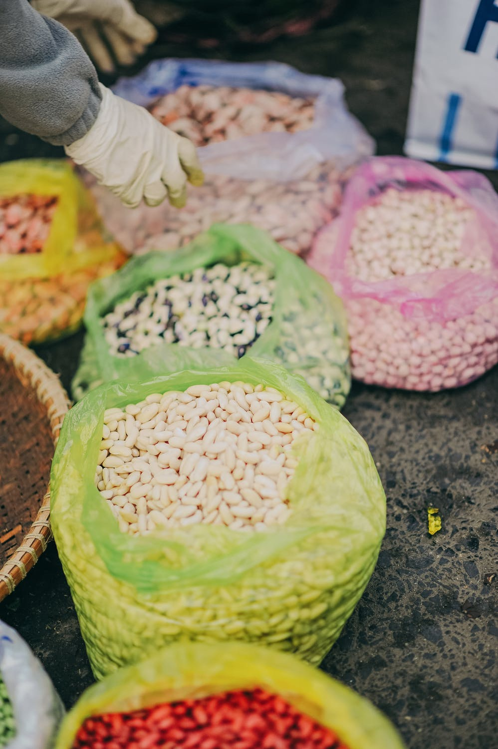 mixed beans in different bags at a market