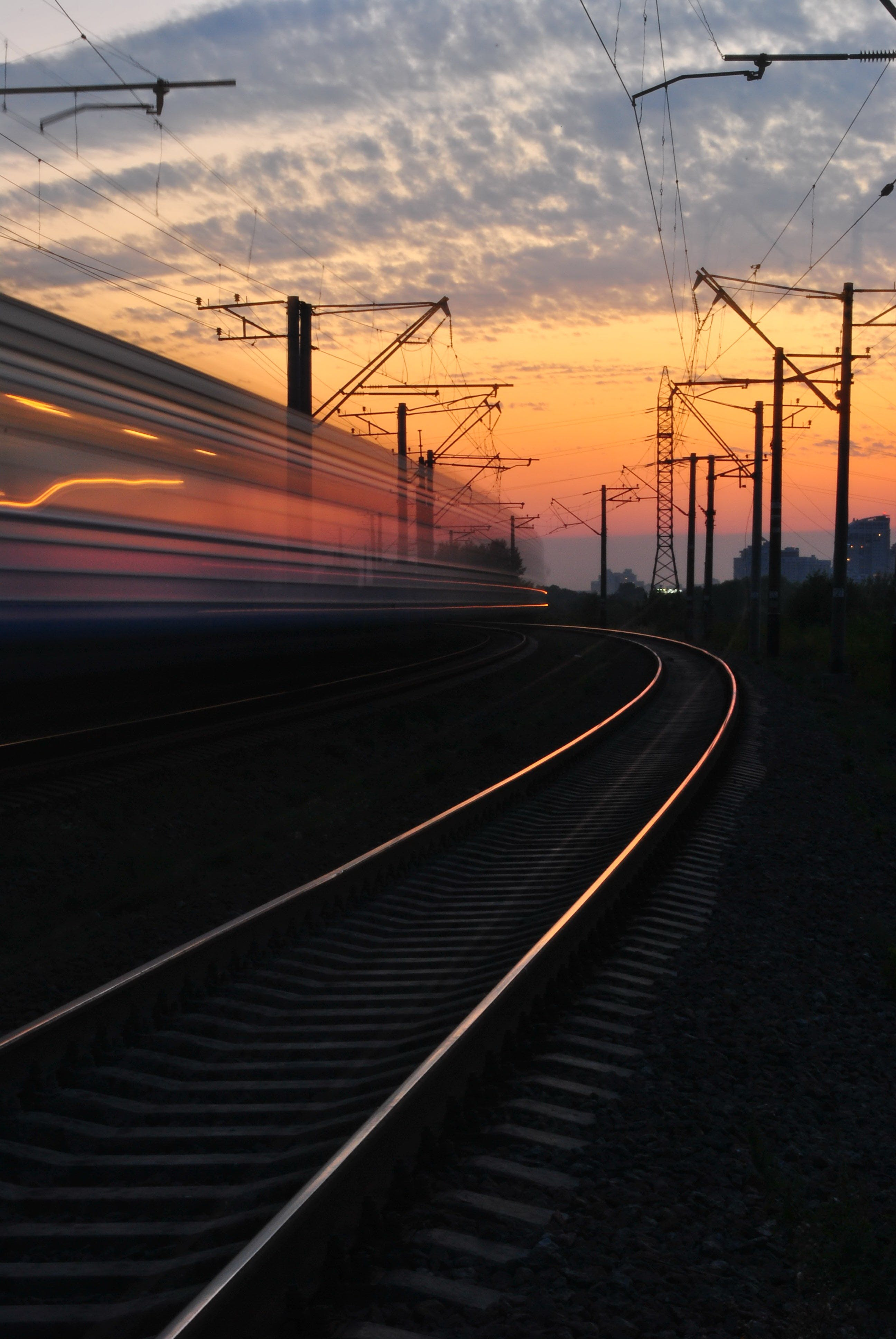 Rail Road Under Gray and Orange Cloudy Sky during Sunset