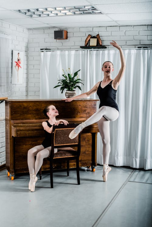 Woman Dancing Ballet Beside Girl Sitting on Chair