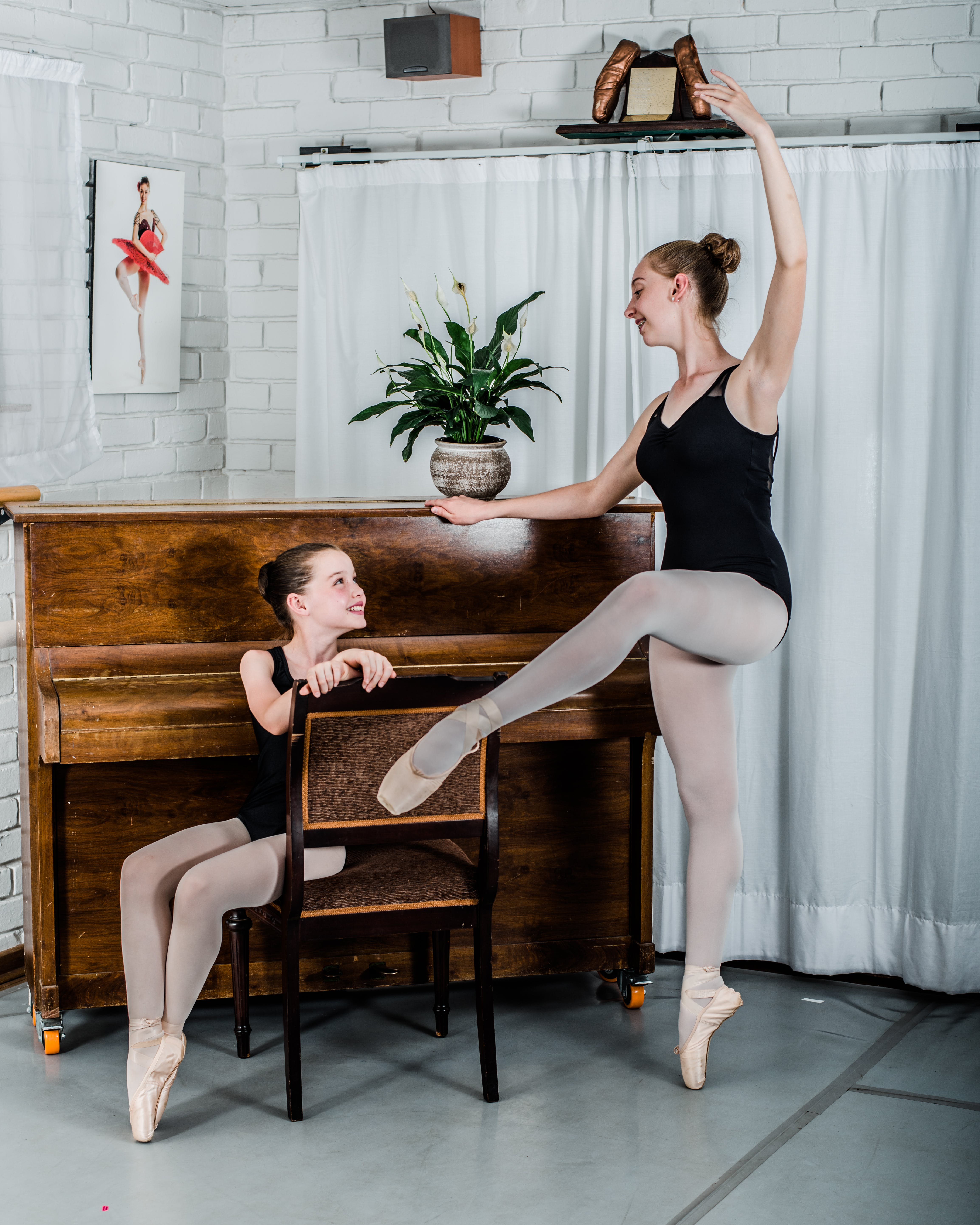 Woman Dancing Ballet in Front of Girl Sitting on Chair