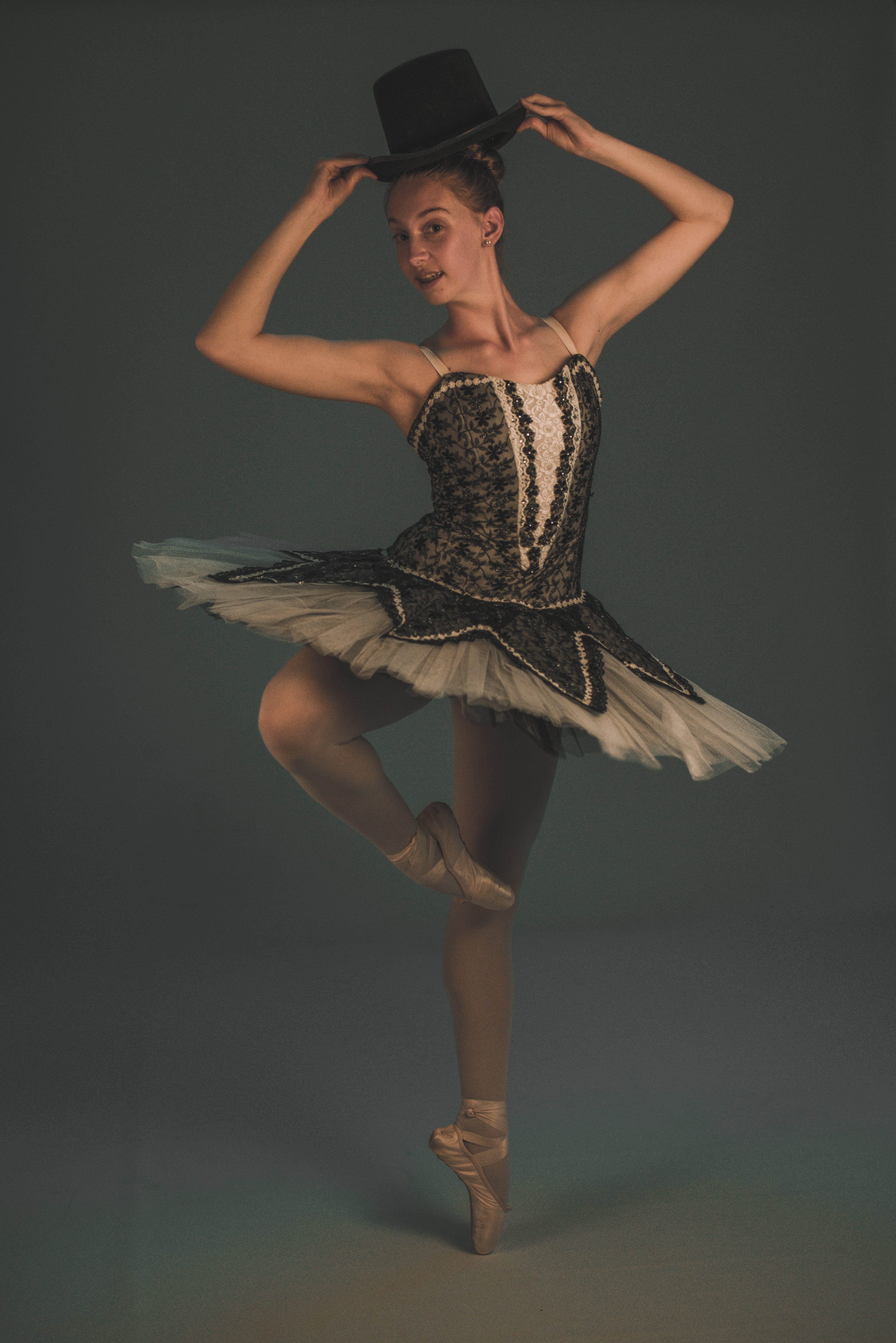 Ballerina in Dance Form Holding Her Black Hat