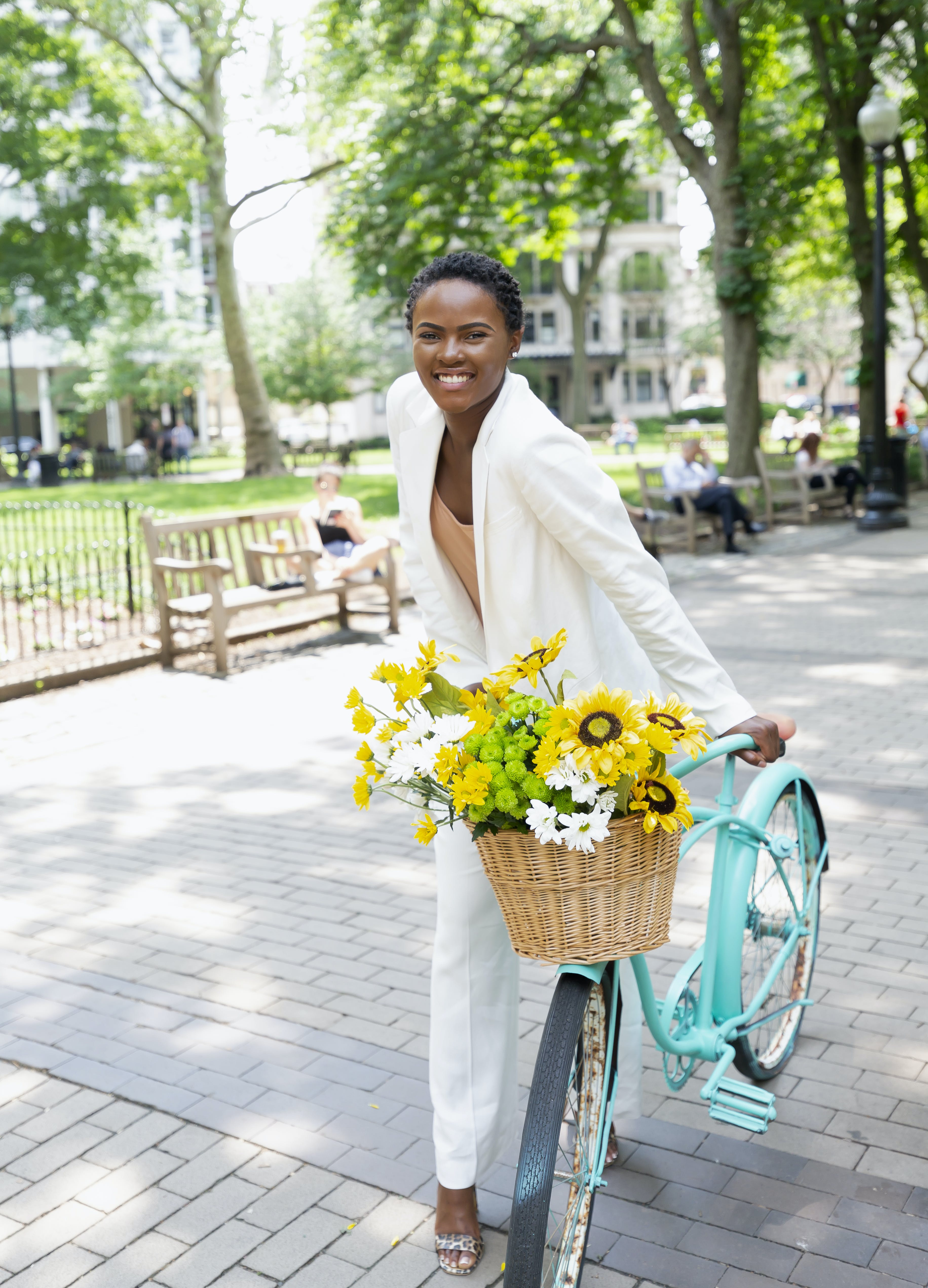 Smiling Woman Holding Blue Cruiser Bike With Basket of Flowers on Park Near People Sitting on Benches
