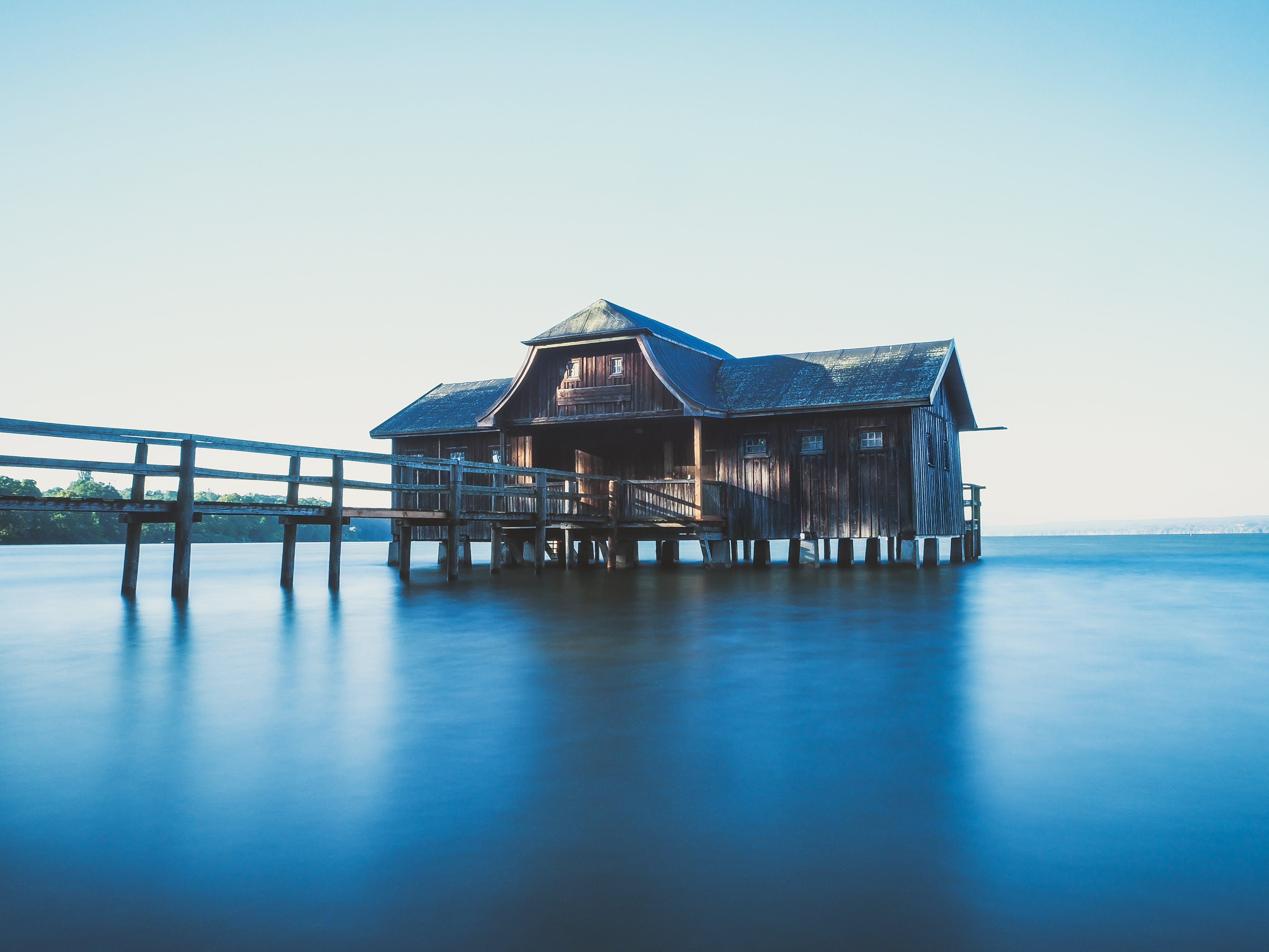 Brown Wooden House on Body of Water With Dock