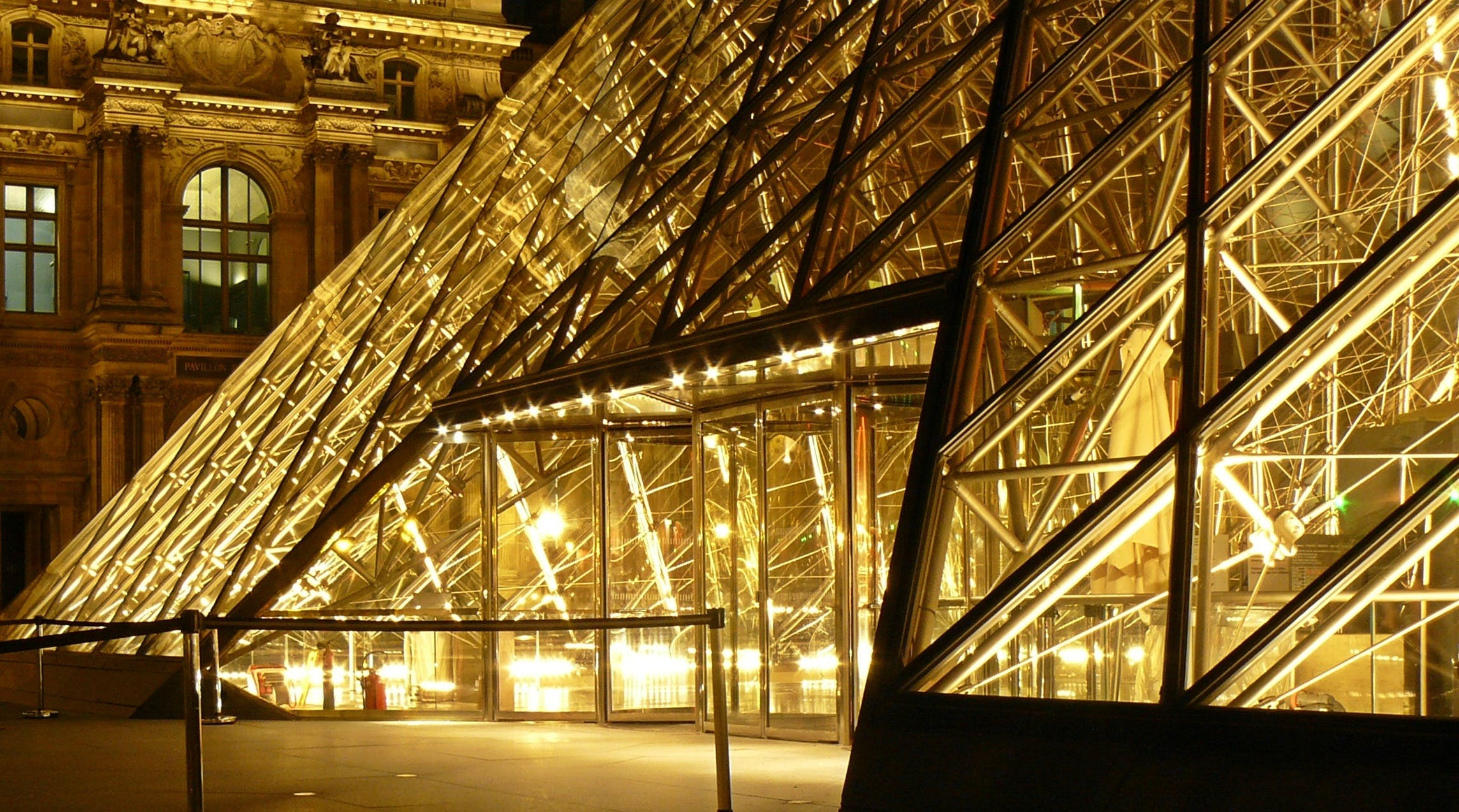 Metal Frame Glass Pyramid Outside a Museum With Yellow Lights during Nighttime