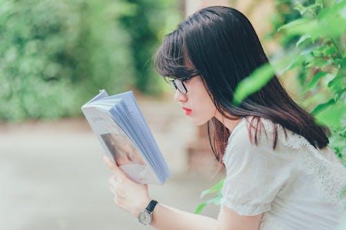 Kostenloses Stock Foto zu asiatische frau, brille, buch, draußen