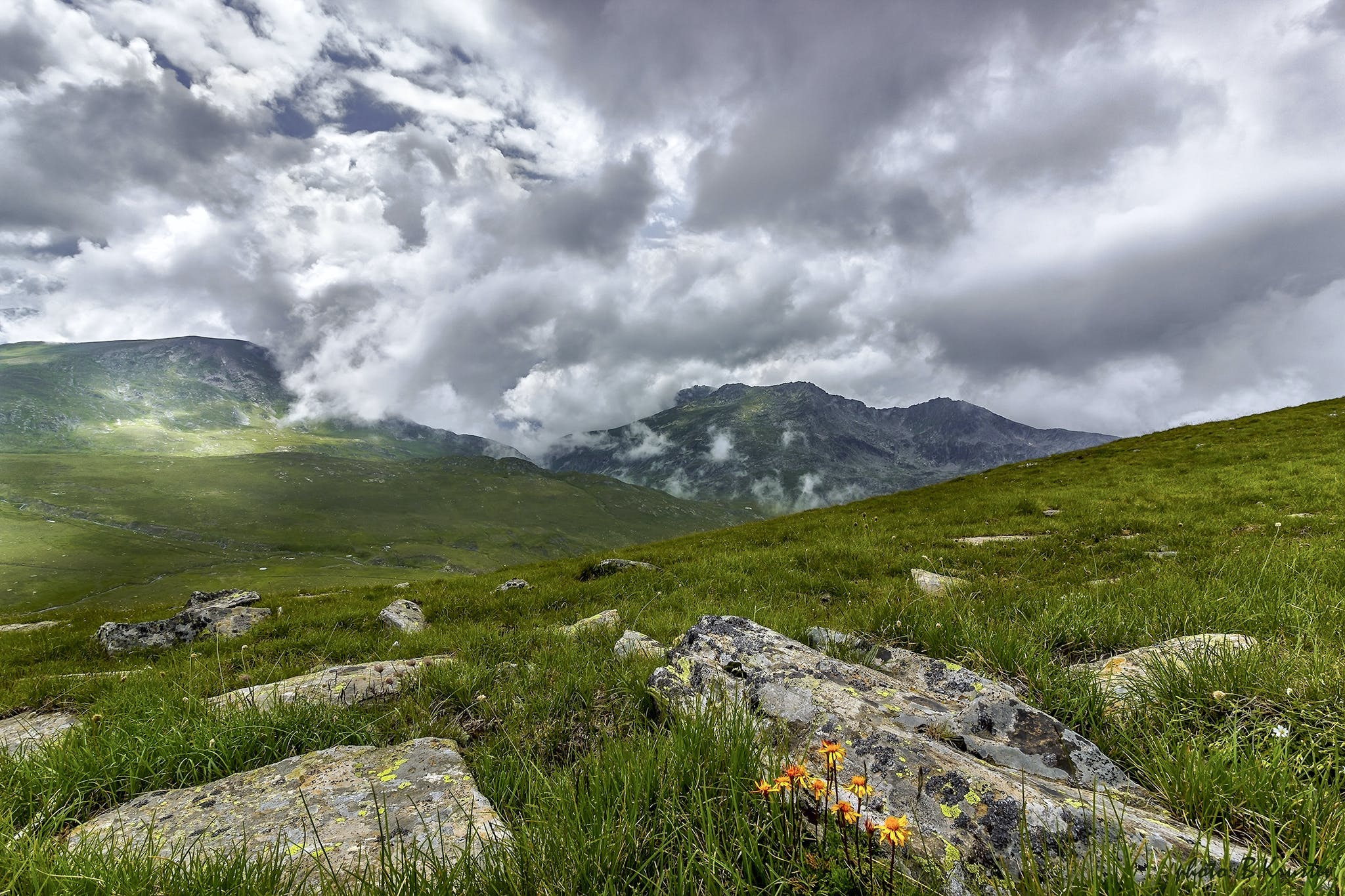 Green Grass Field With Rocks Near Mountains during Cloudy Daytime Sky