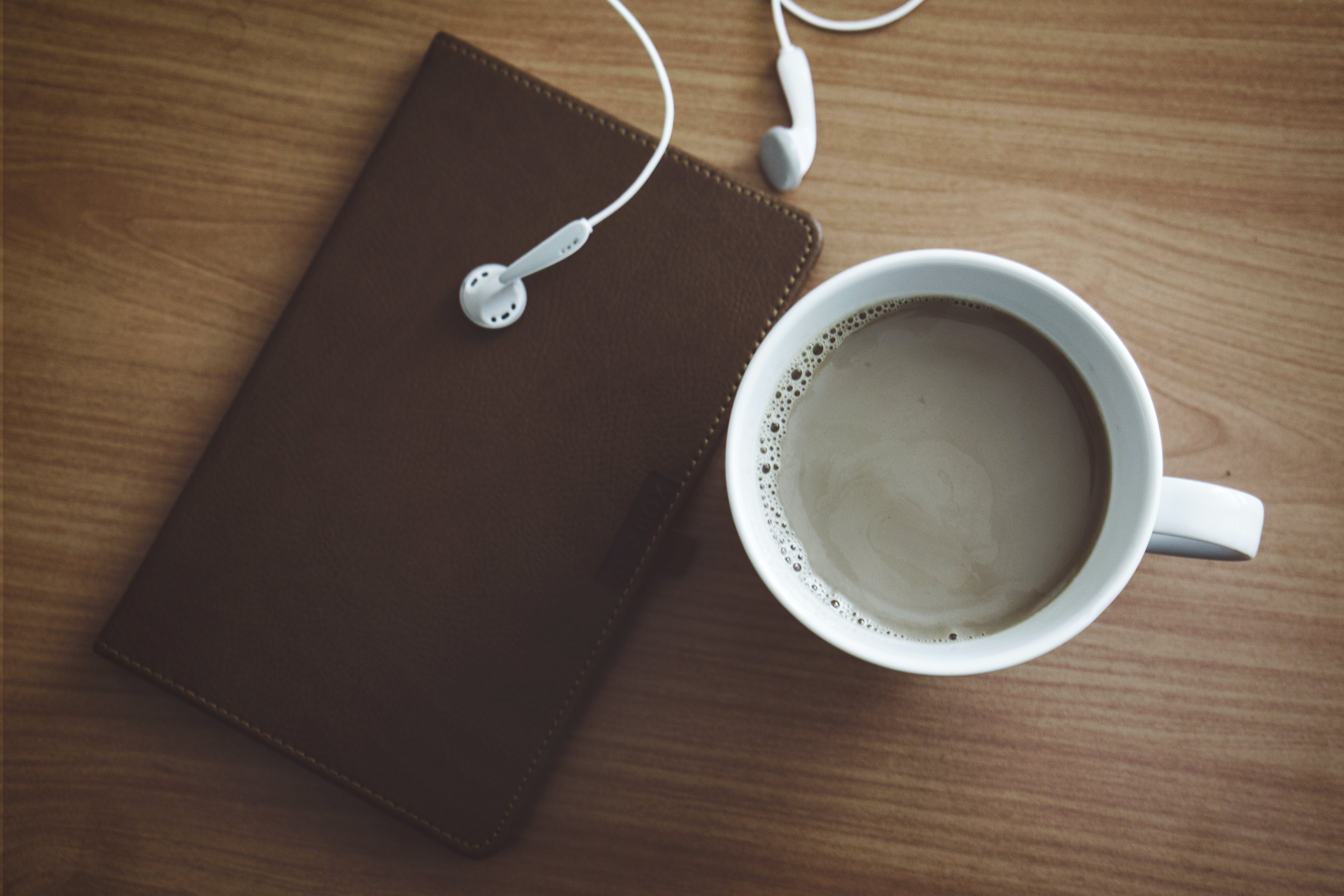White Mug Beside Wallet and Earbuds