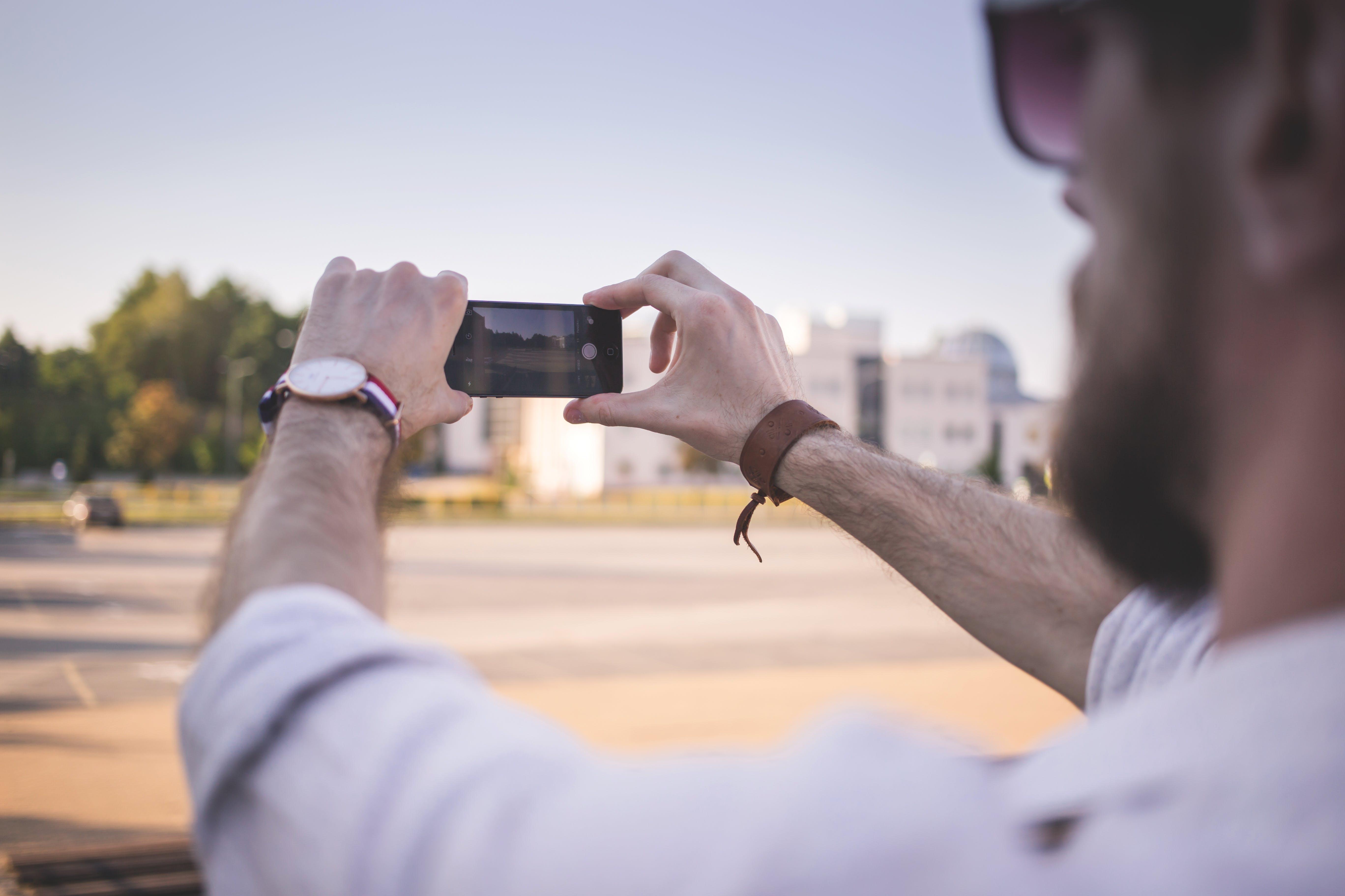 Tilt Shift Photo of Man Holding Black Smartphone Taking Photo of Gray Ground at Daytime