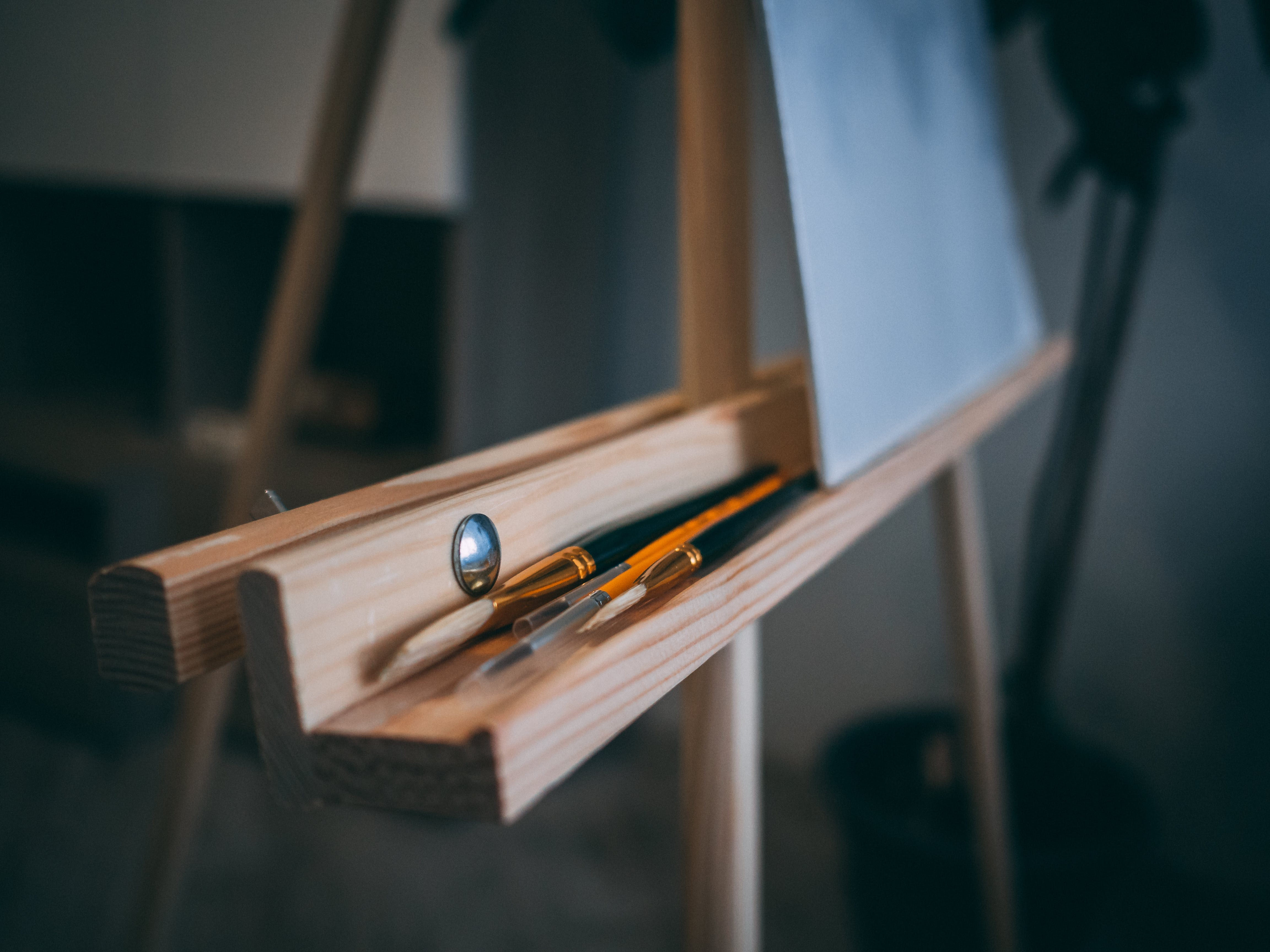 Brown Easel With Pens and Brushes
