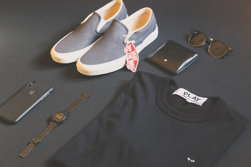 Pair of Gray Vans Low-top Sneakers Beside Black Shirt, Sunglasses, and Watch