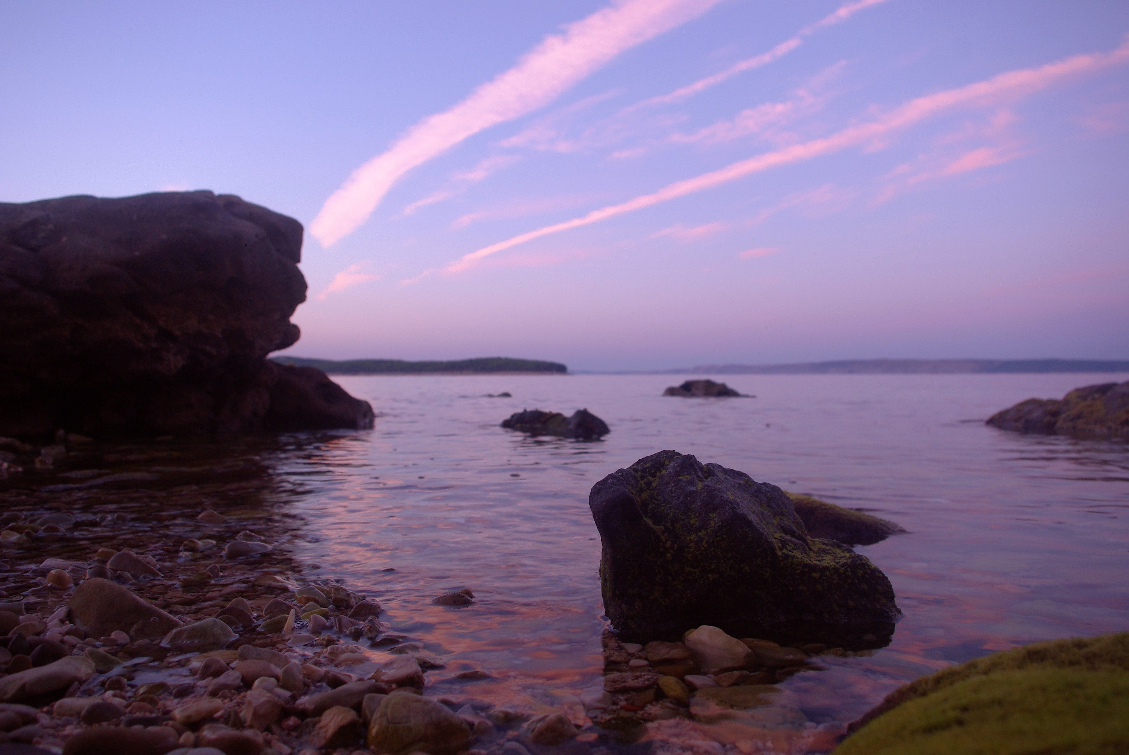 Rock Formation on Body of Water Under Altostratus Clouds