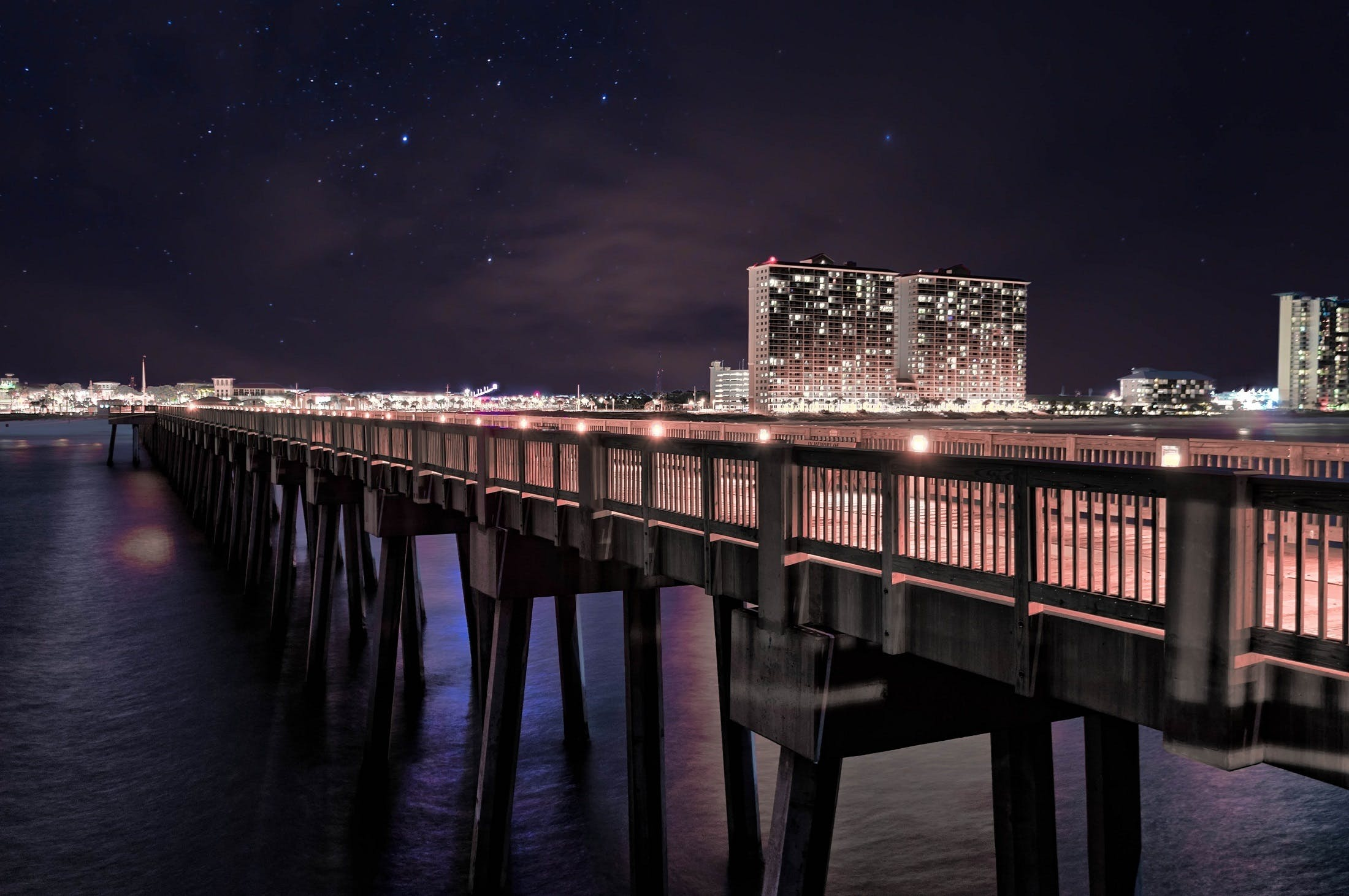 Bridge on Body of Water Near High Rise Building during Night Time Photo