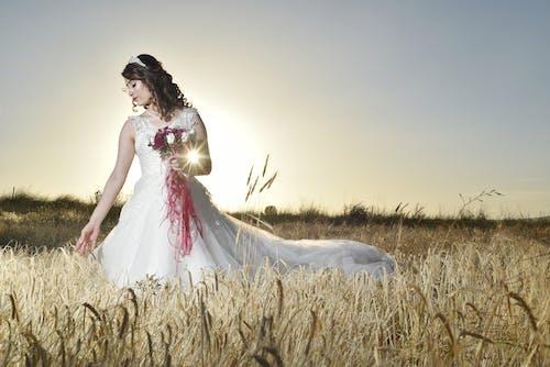 흰색 신부 드레스는 Feld에 서있는 여자