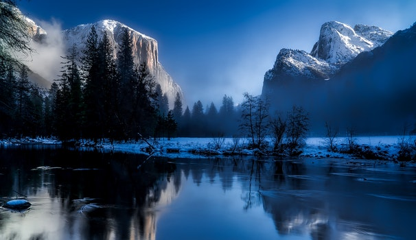 Body of Water Beside Trees by Snowfield Near Mountains