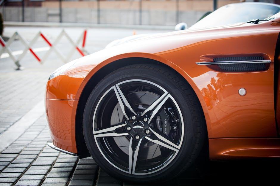 Orange Car Parked Near Grey Triangular Sign during Daytime