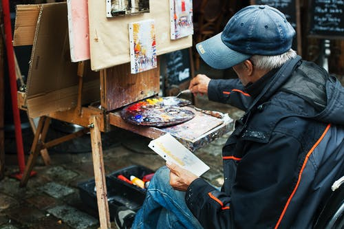 Man Holding Brush While Painting in Front of Easel