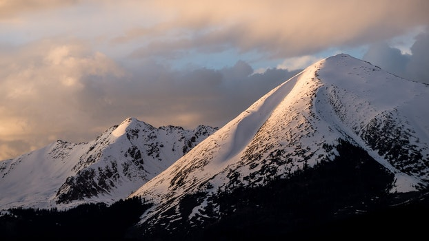 Mountain With Snow Under Cloudy Skies