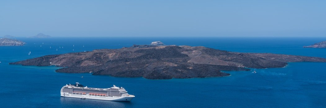 White Crewship Near Island Under Clear Sky at Daytime