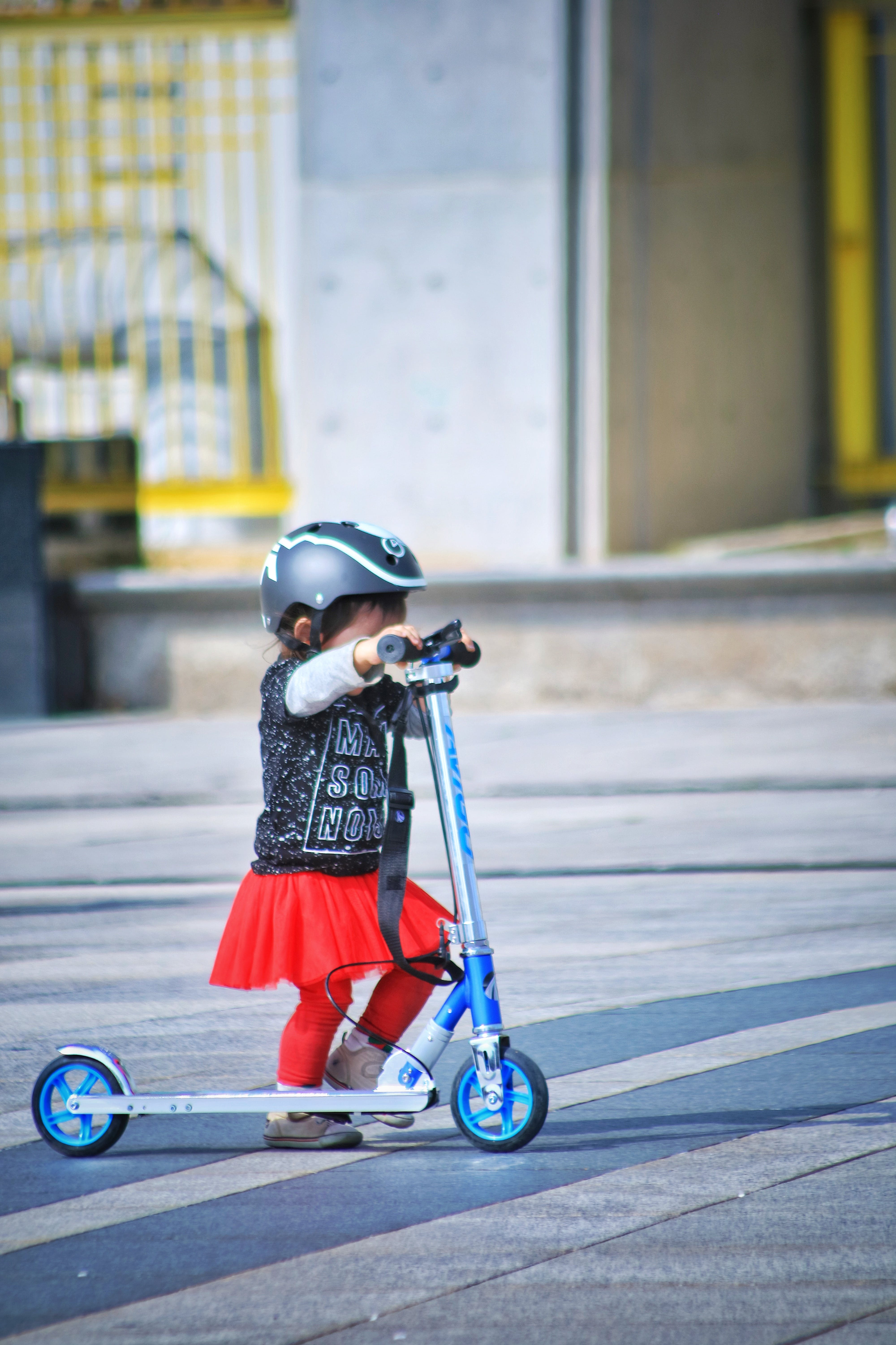 Toddler Using Scooter on Road